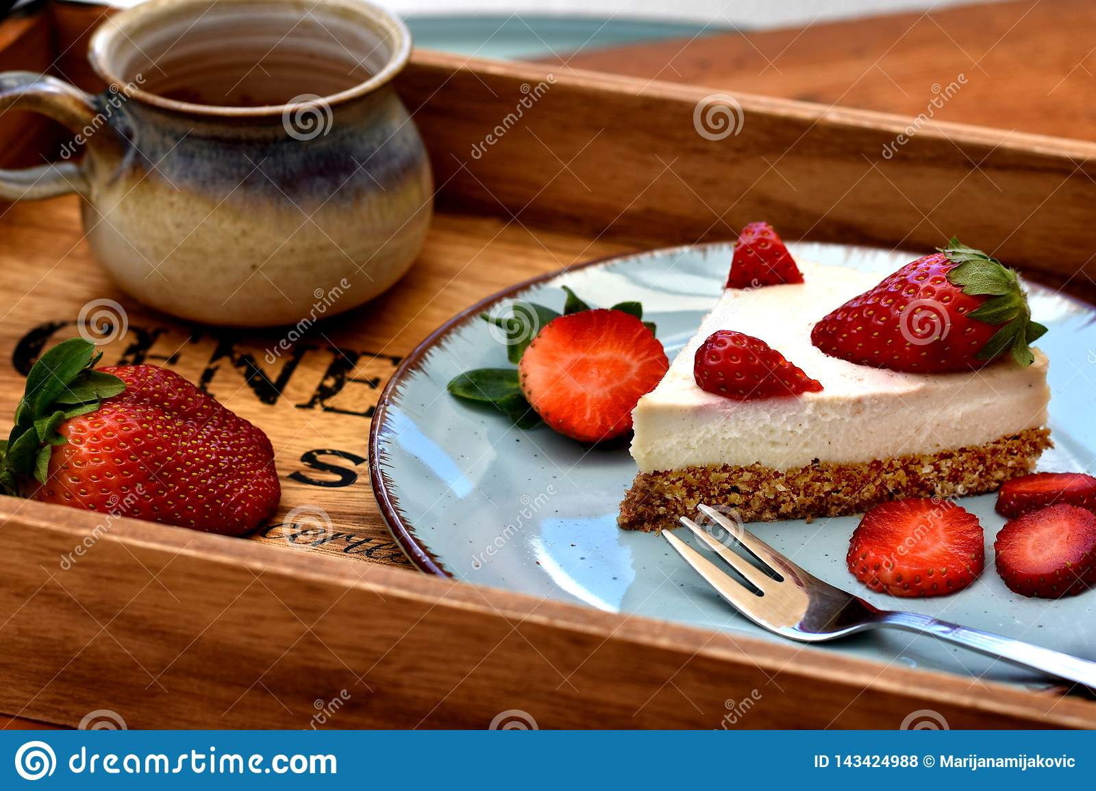 Slice of raw white strawberry cake on a blue plate with cup of coffee. Healthy breakfast concept.