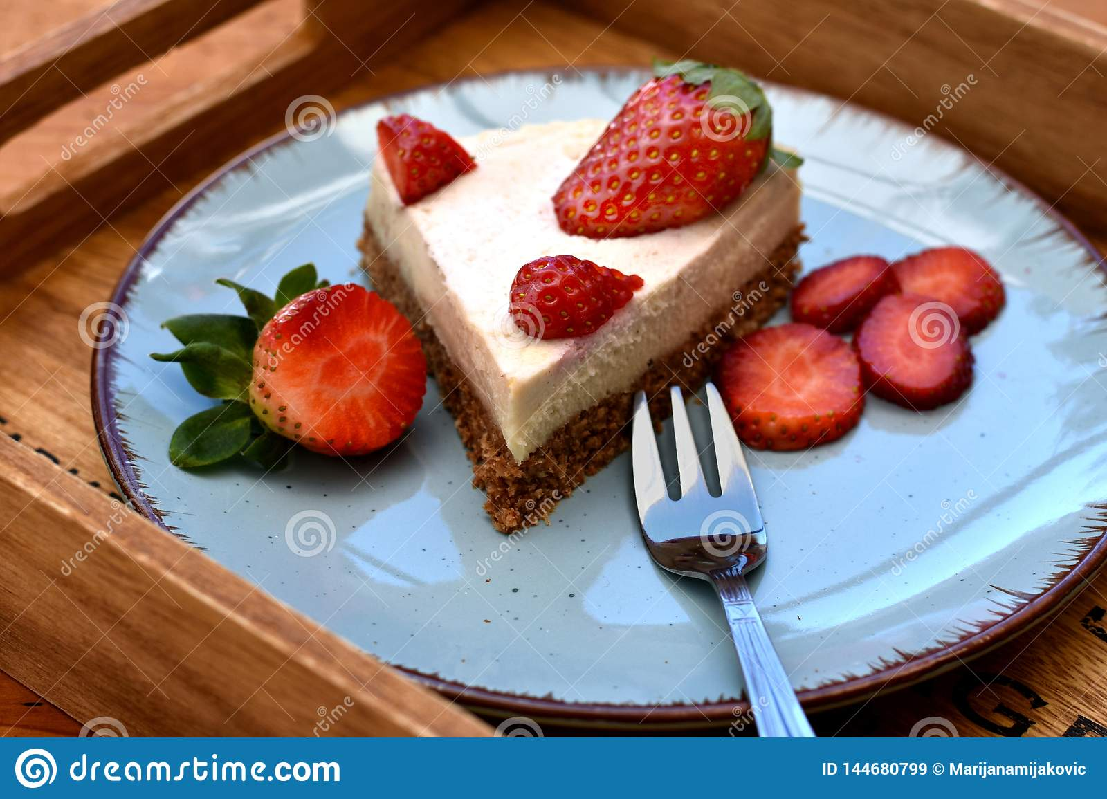 Slice of raw strawberry cake on blue plate