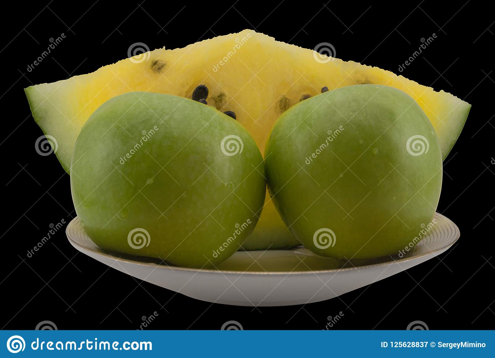 The slice of yellow watermelon and green apples on the plate.