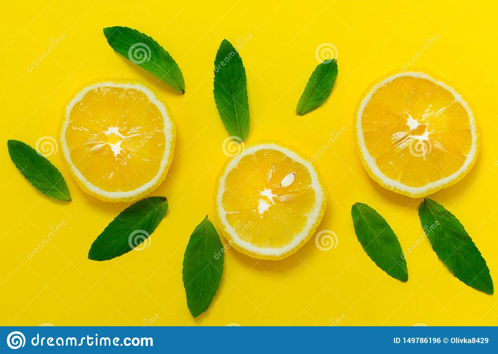 Sliced ​​lemon and mint leaves on a bright yellow background. Background for the design of banners, websites.