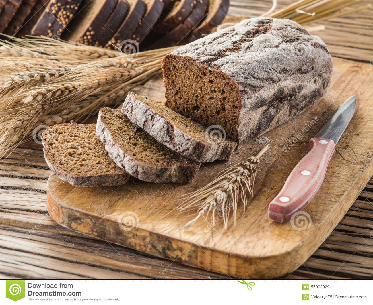 Sliced black bread on the wooden plank.