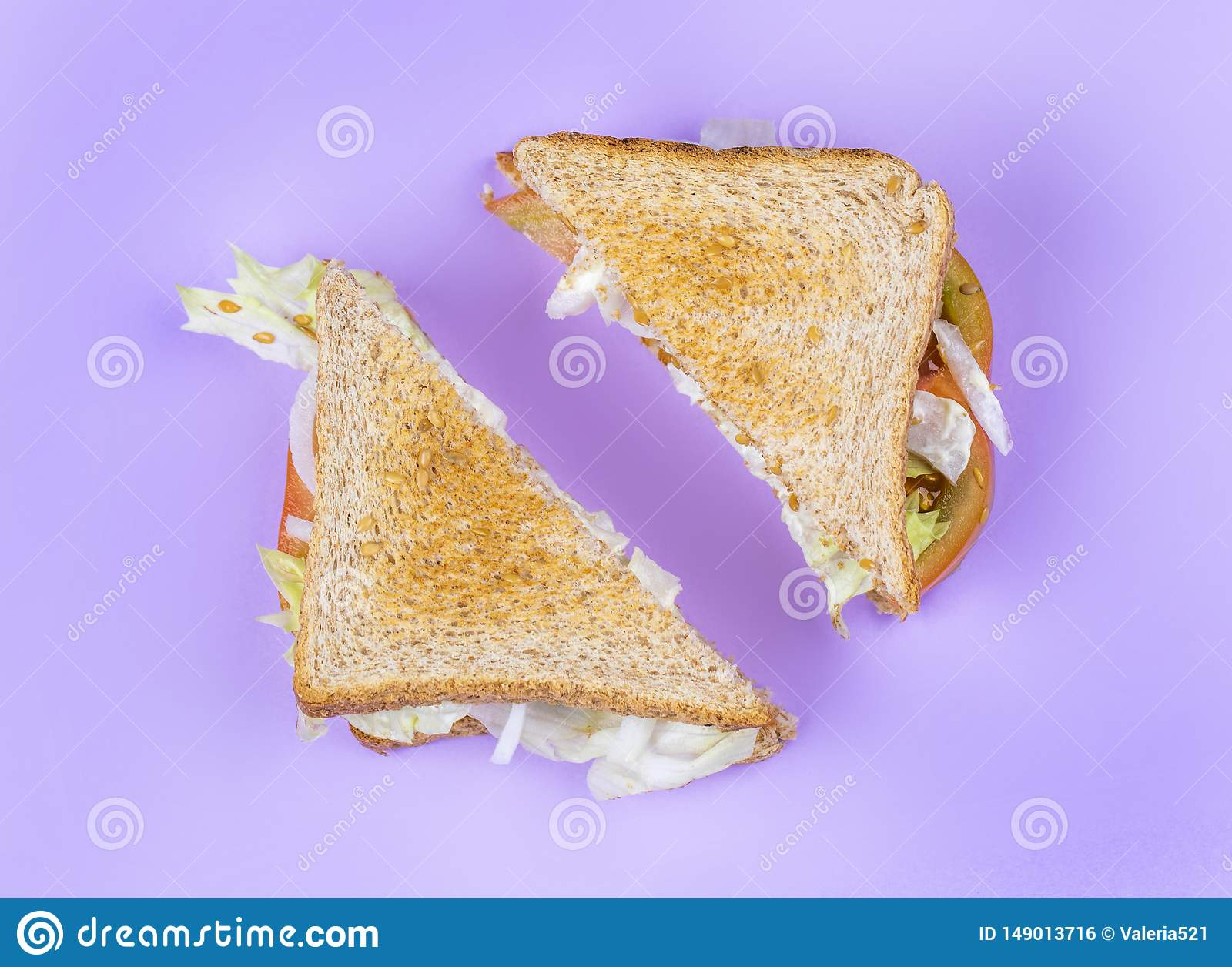 Sliced club sandwich on light violet background with tomatoes, onions, sesame and salade. Healthy food. Flat lay