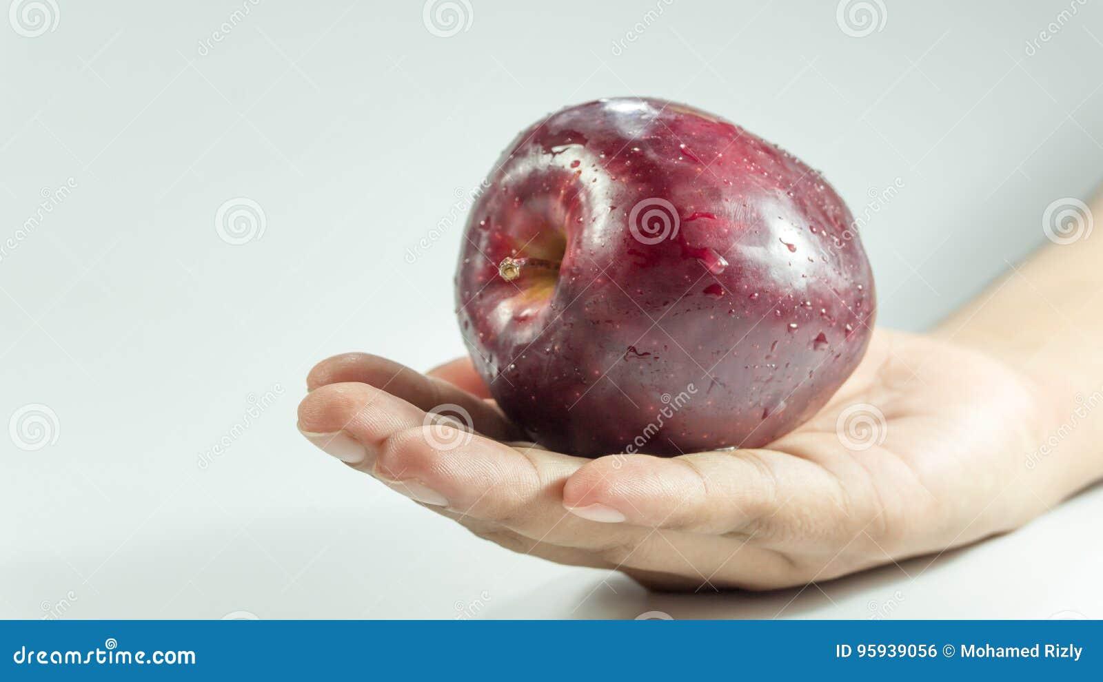 Sliced cube of fresh Red appleon hand.