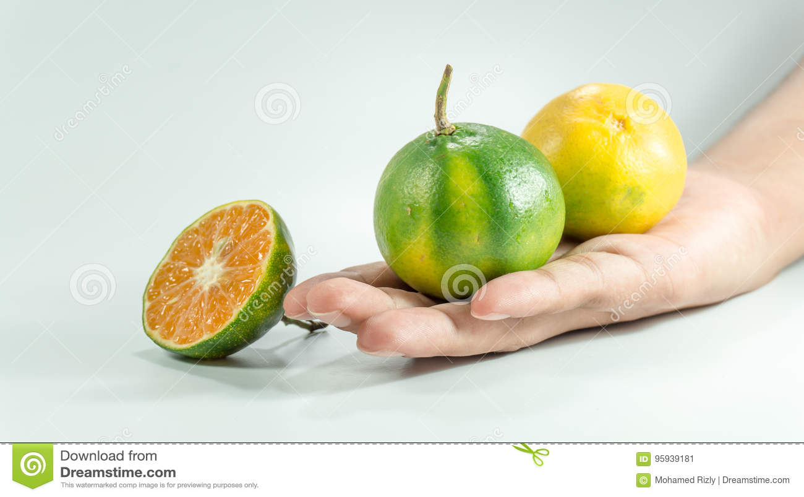 Sliced cube of fresh tangerine and one tangerine on hand.