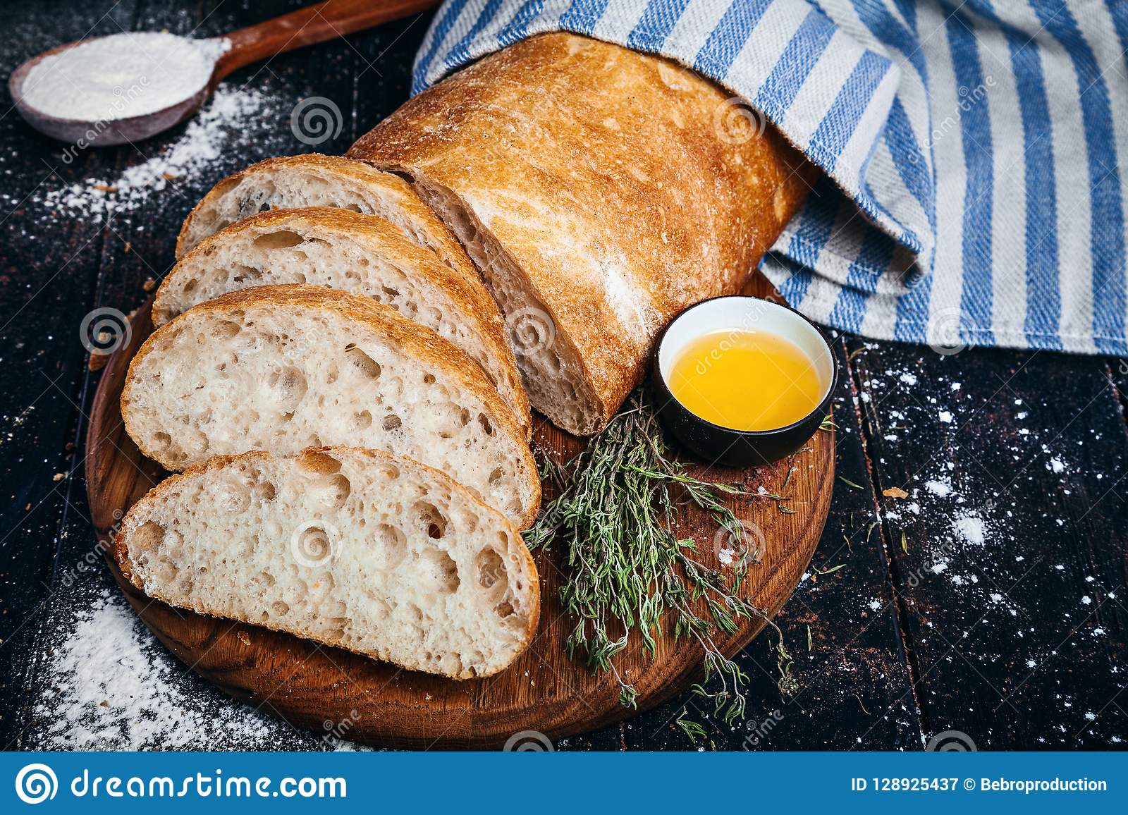 Sliced homemade italian ciabatta bread with olive oil on dark background. Ciabatta, herbs, olive oil, flour. Close up view, copy s