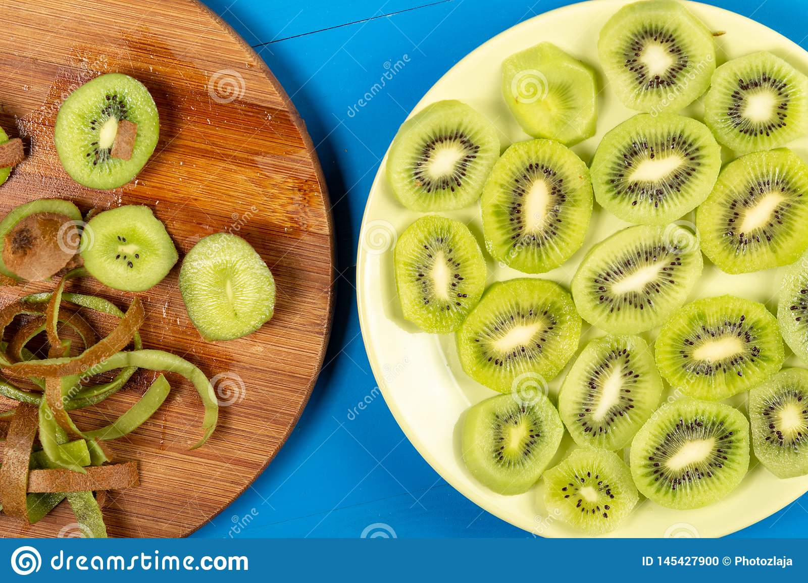 Sliced Kiwi Fruit On The Plate and Wooden Cutting Board