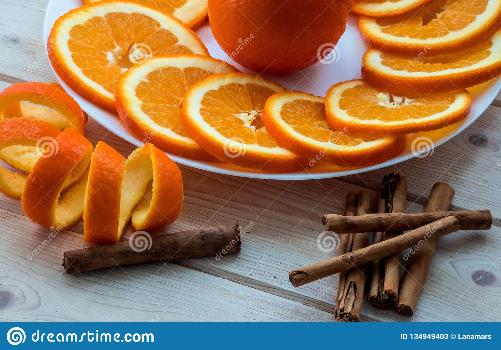 Sliced orange with spiral zest on the plate and cinnamon sticks on the wooden table