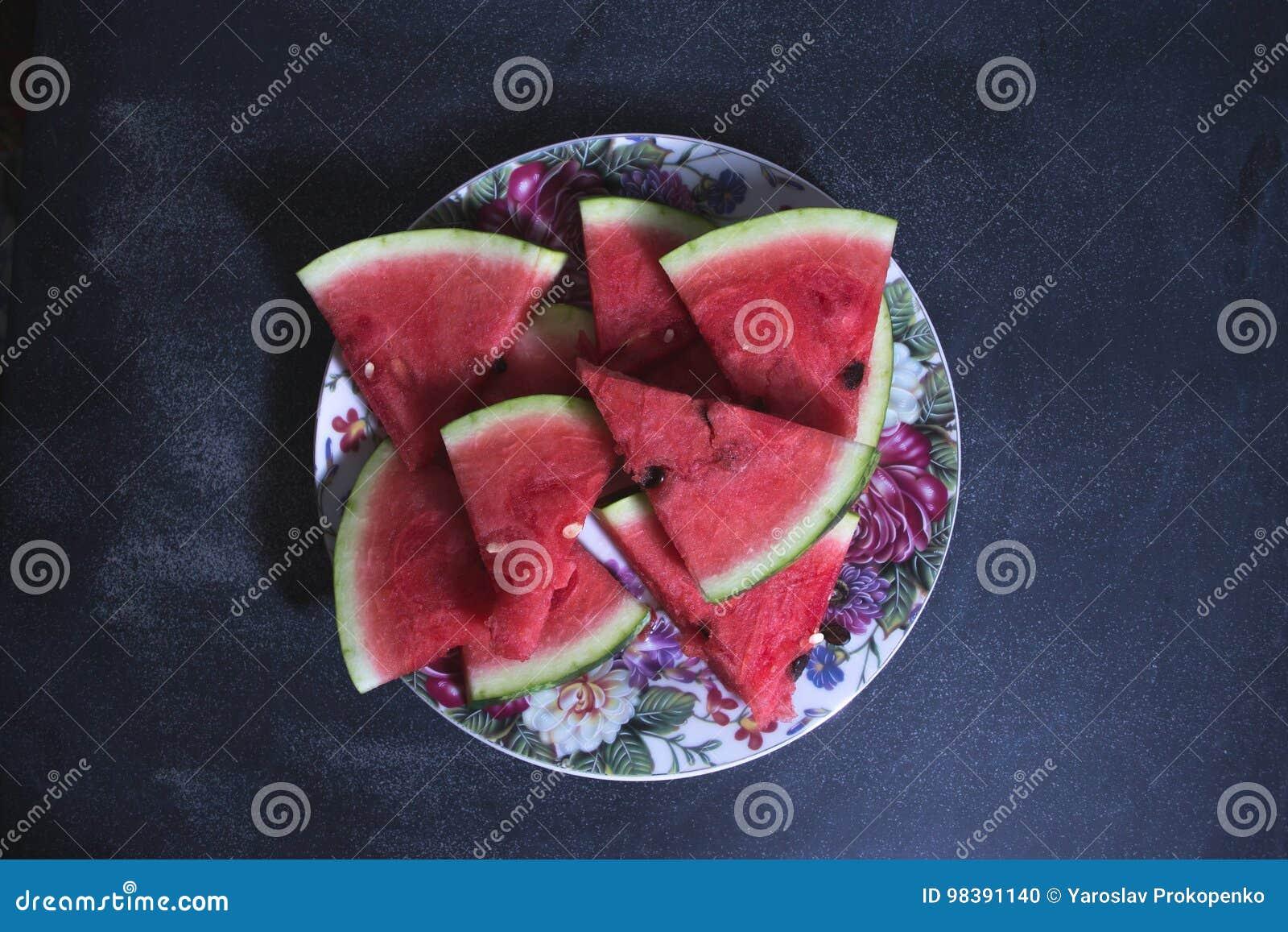 Sliced slices of watermelon on a dark background.