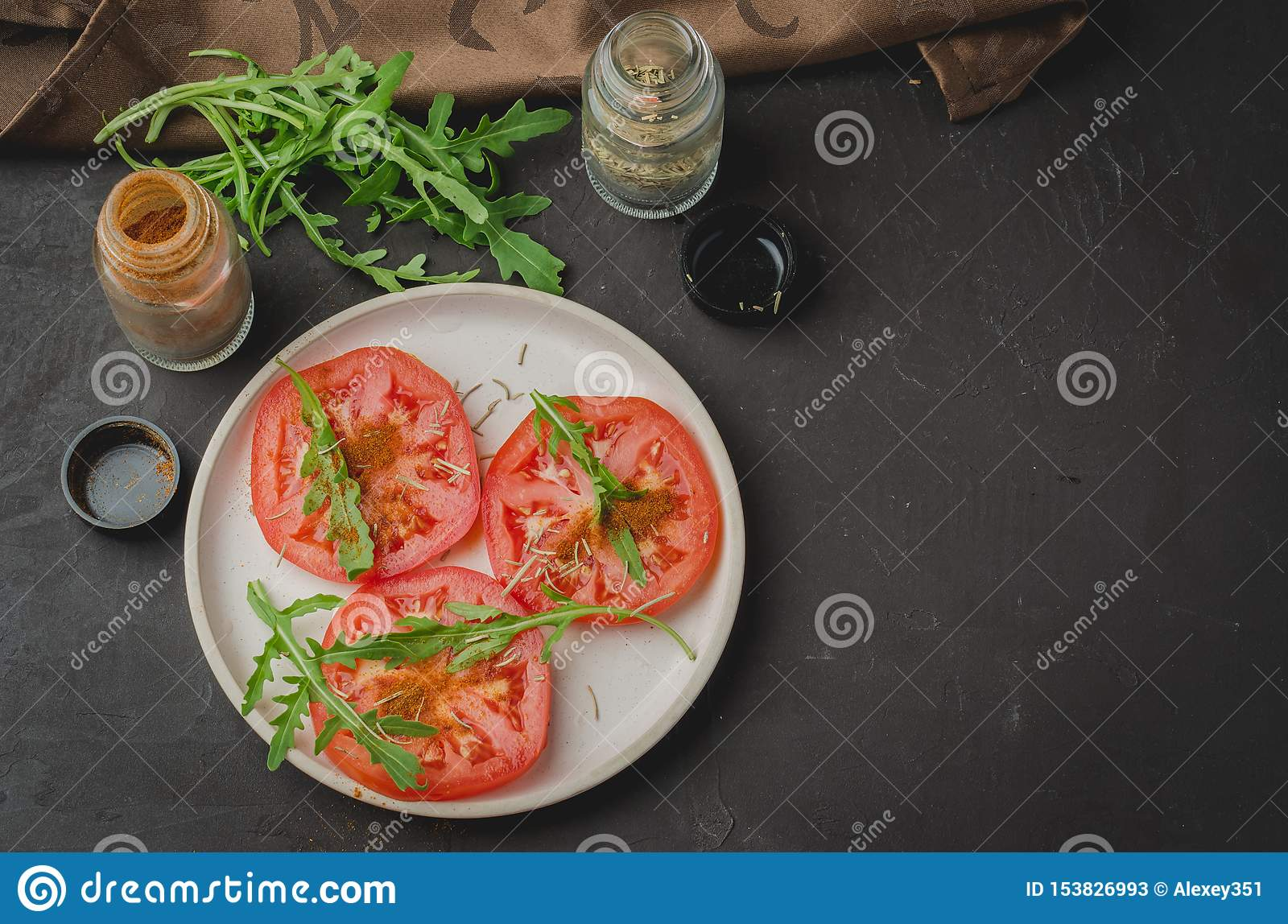 Sliced tomatoes and arugula spices salad. Healthy food salad on a dark background. Copy space and top view