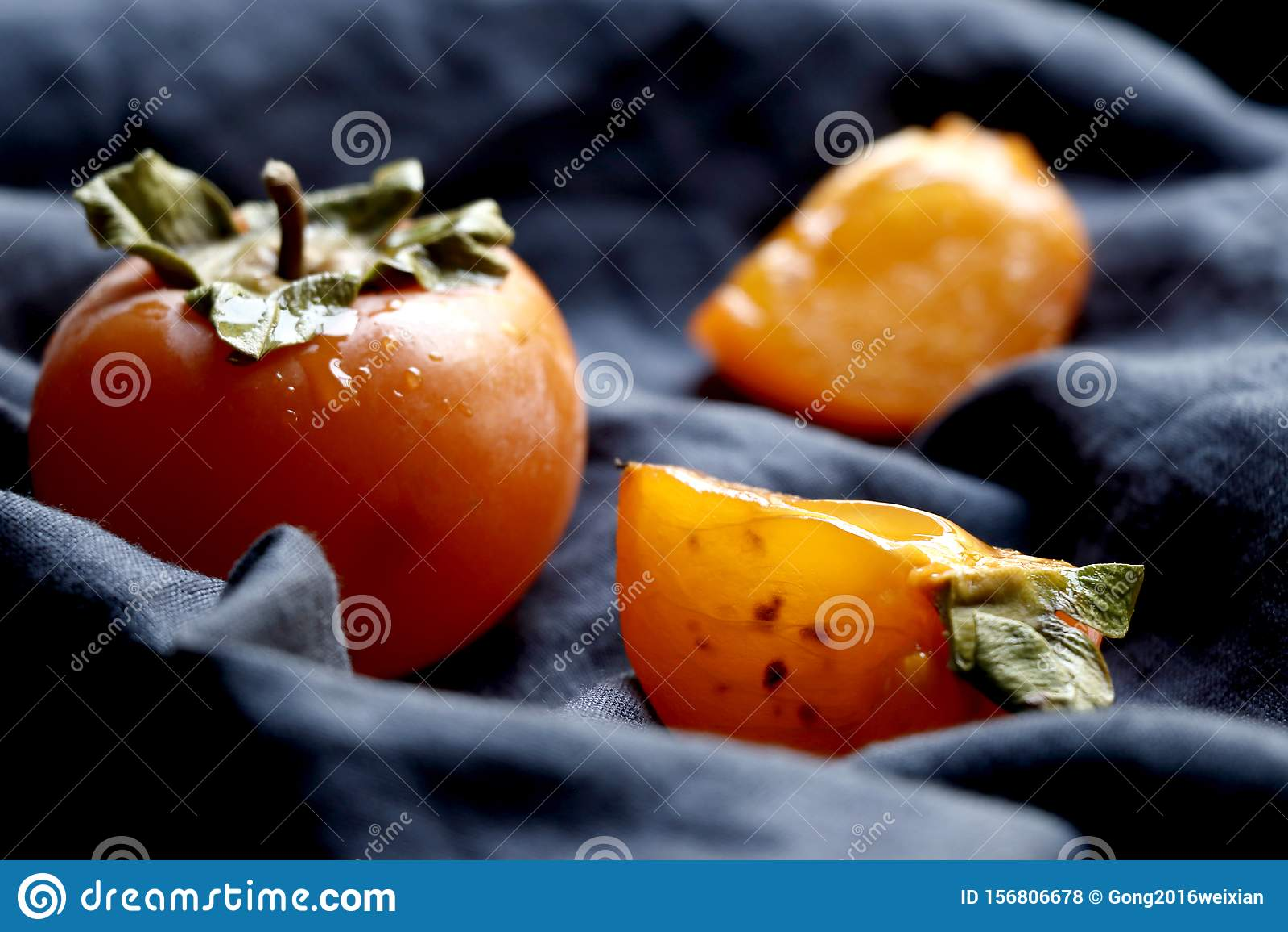 Slices of Orange red persimmon fruit.Fresh kaki on classical blue cloth.