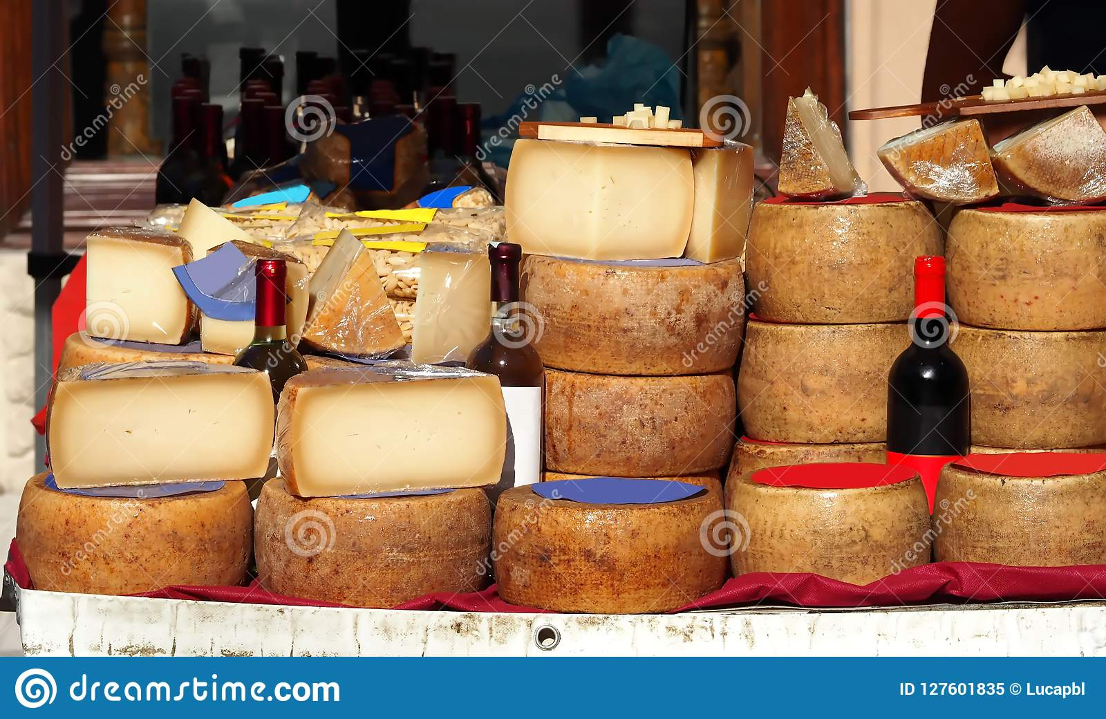 Slices and wheels of Pecorino cheese together with bottles of Cannonau, white wine, pasta and other Sardinian typical dishes