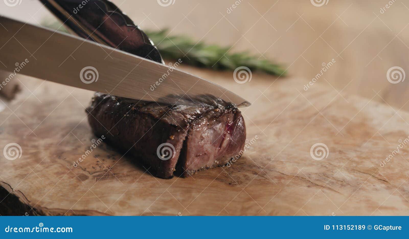 Slicing rare fillet mignon steak on wood board