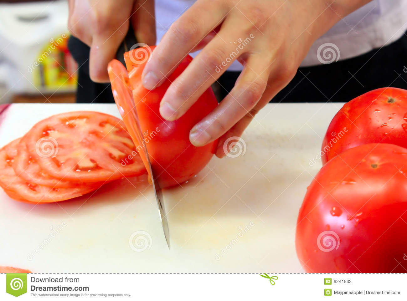 Slicing red juicy tomatoes to put inside hamburgers.