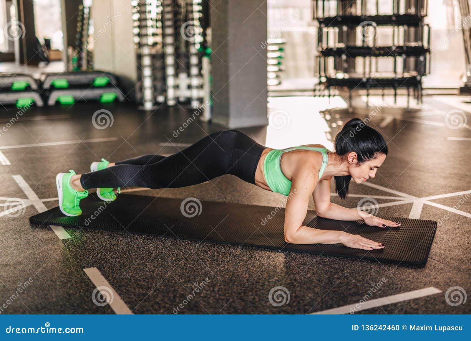 Slim adult sportswoman in plank on mat
