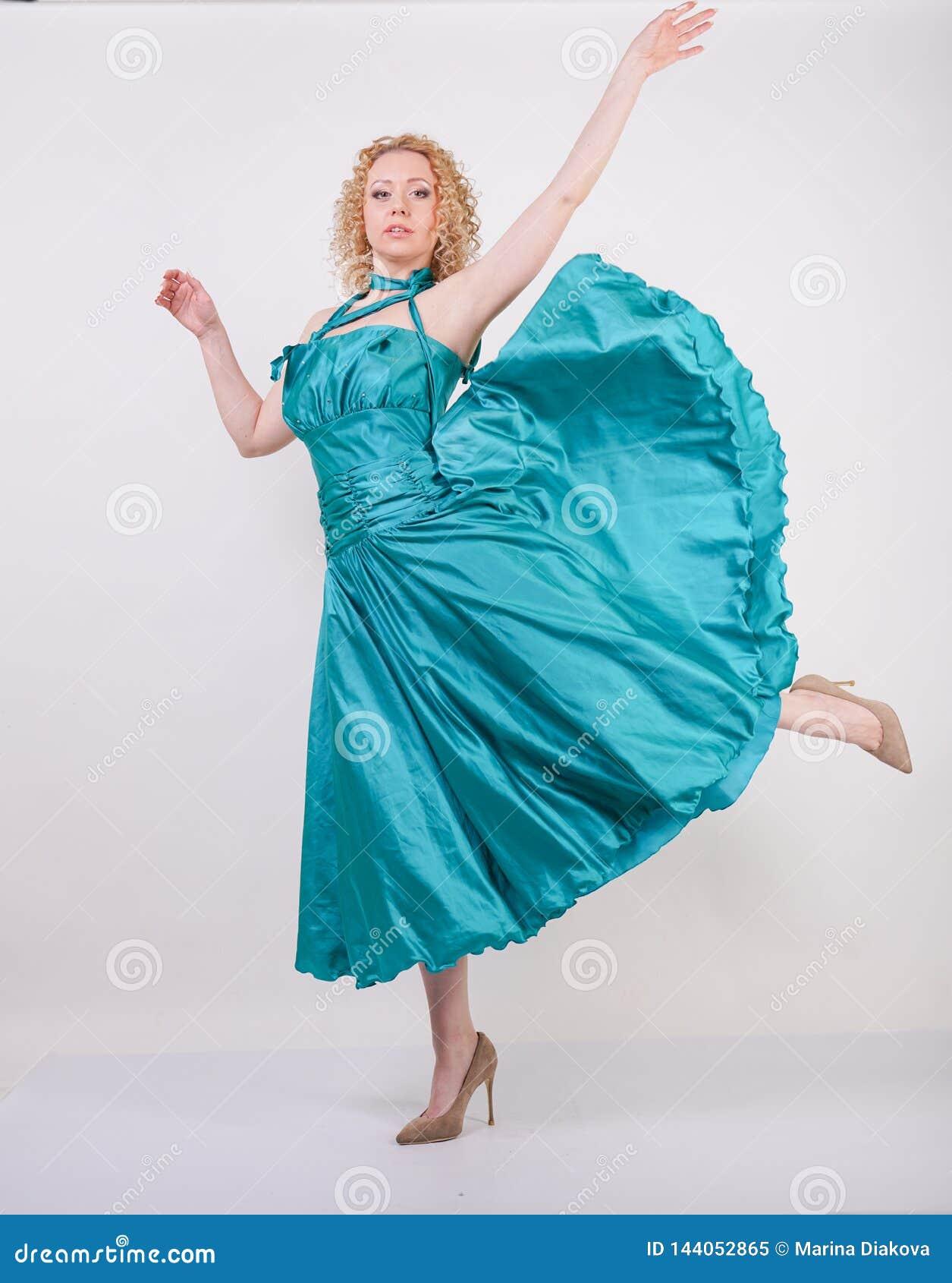 Slim airy girl in flying blue evening dress on white background in Studio