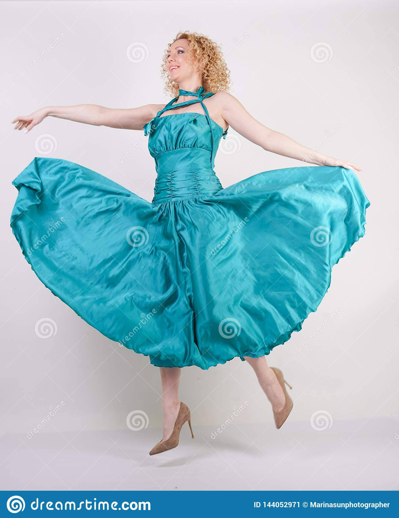Slim airy girl in flying blue evening dress on white background in Studio