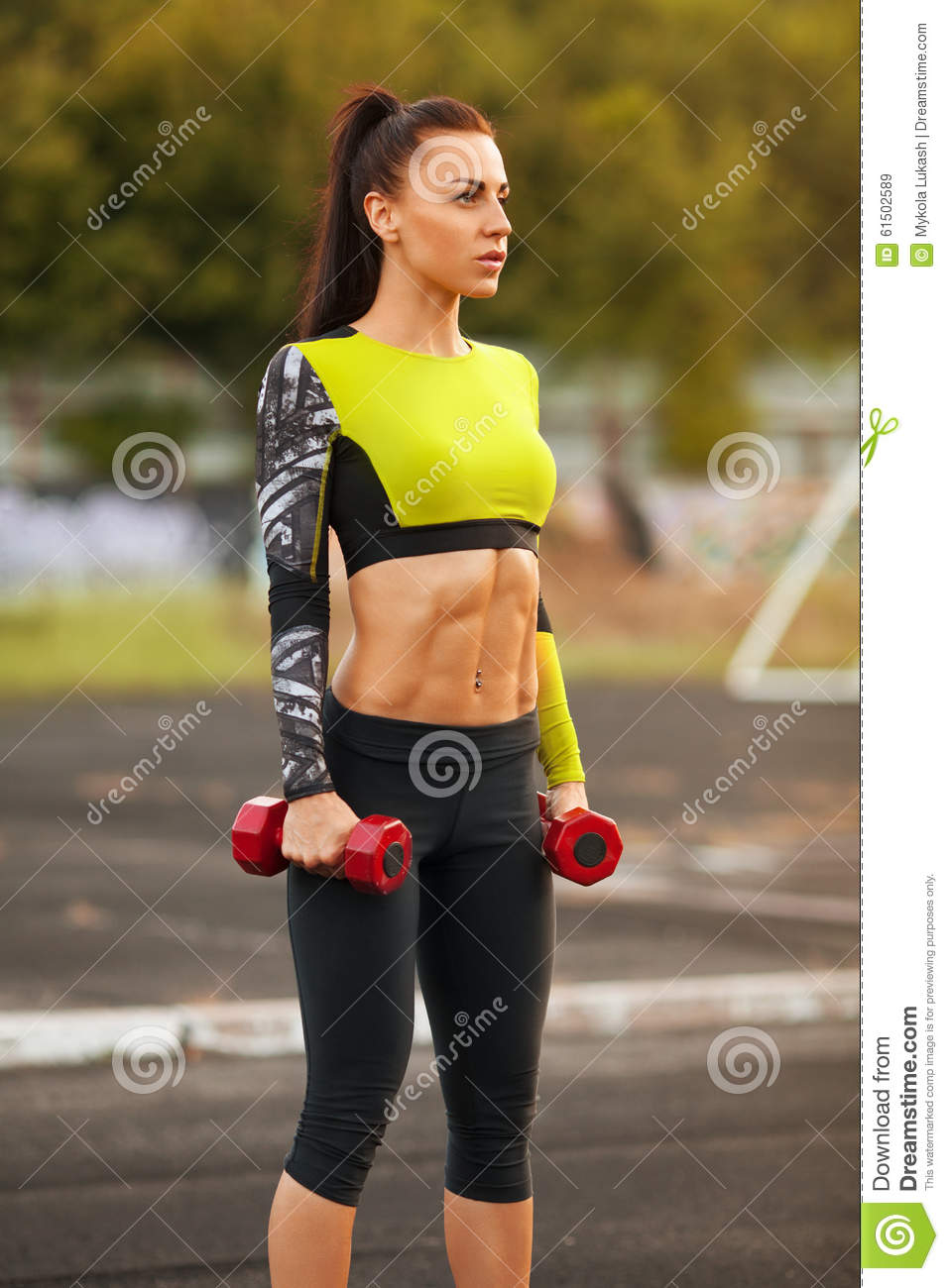 Slim Athletic Woman With Dumbbells In The Stadium. Sporty
