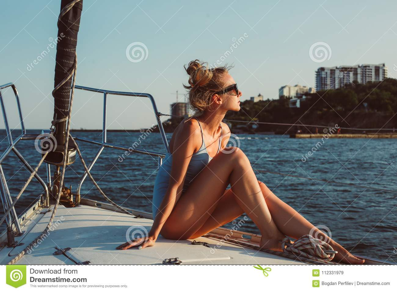 Profile portrait of young woman is sitting on the deck of boat