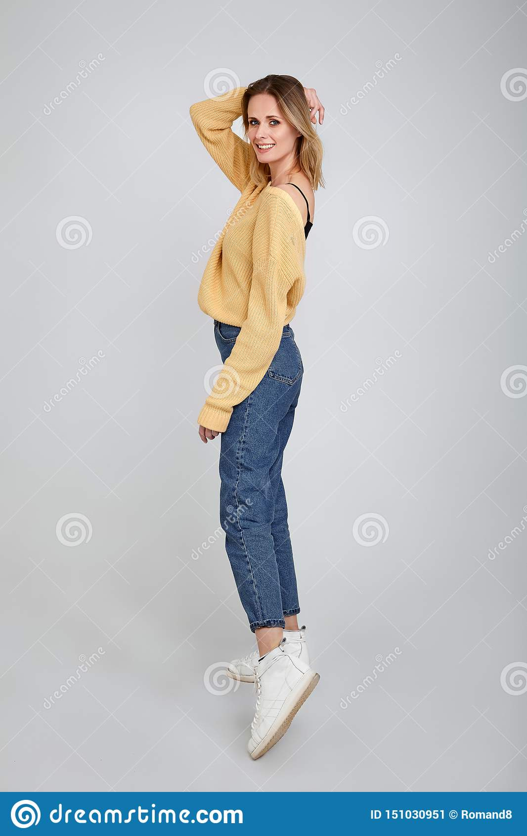 Slim and beautiful. Full length studio shot of attractive young woman in casual wear smiling and holding hair by her hand while