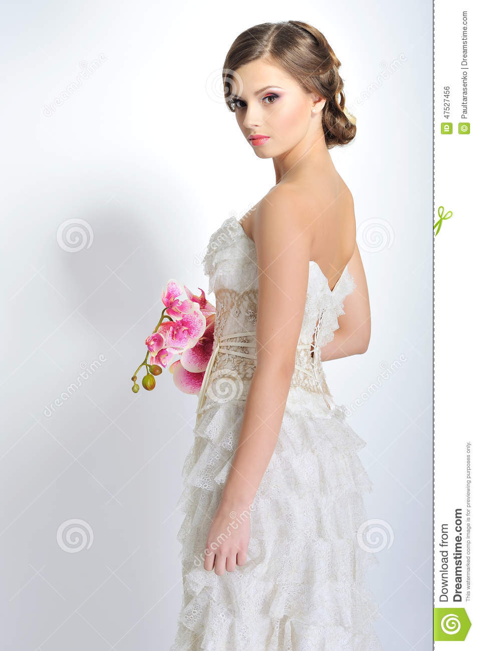 Slim beautiful woman with flowers wearing luxurious wedding dress over white studio background