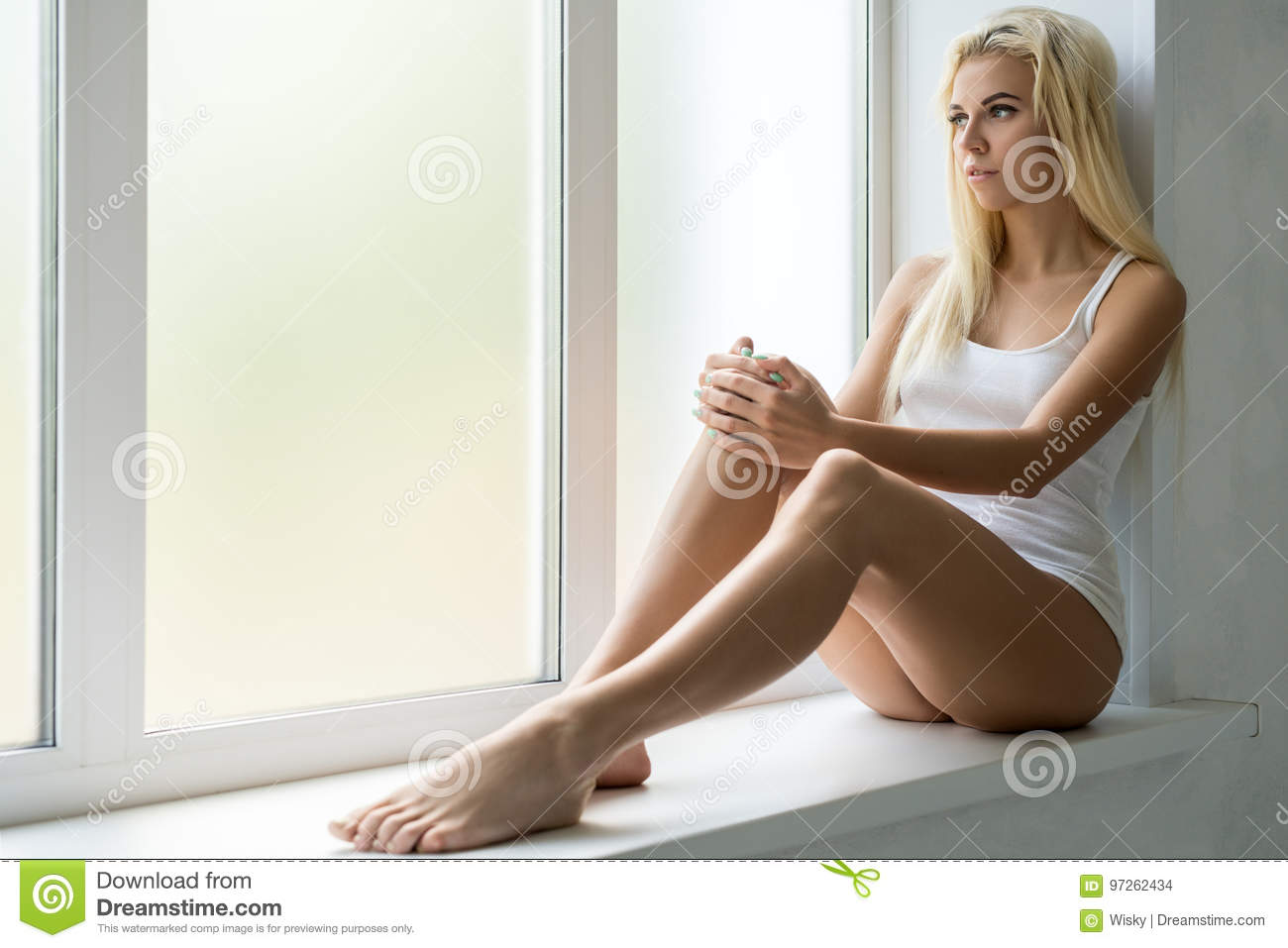 1db4da4d96c5b Young pretty slim blonde wearing white top and shorts sitting on window  sill in studio
