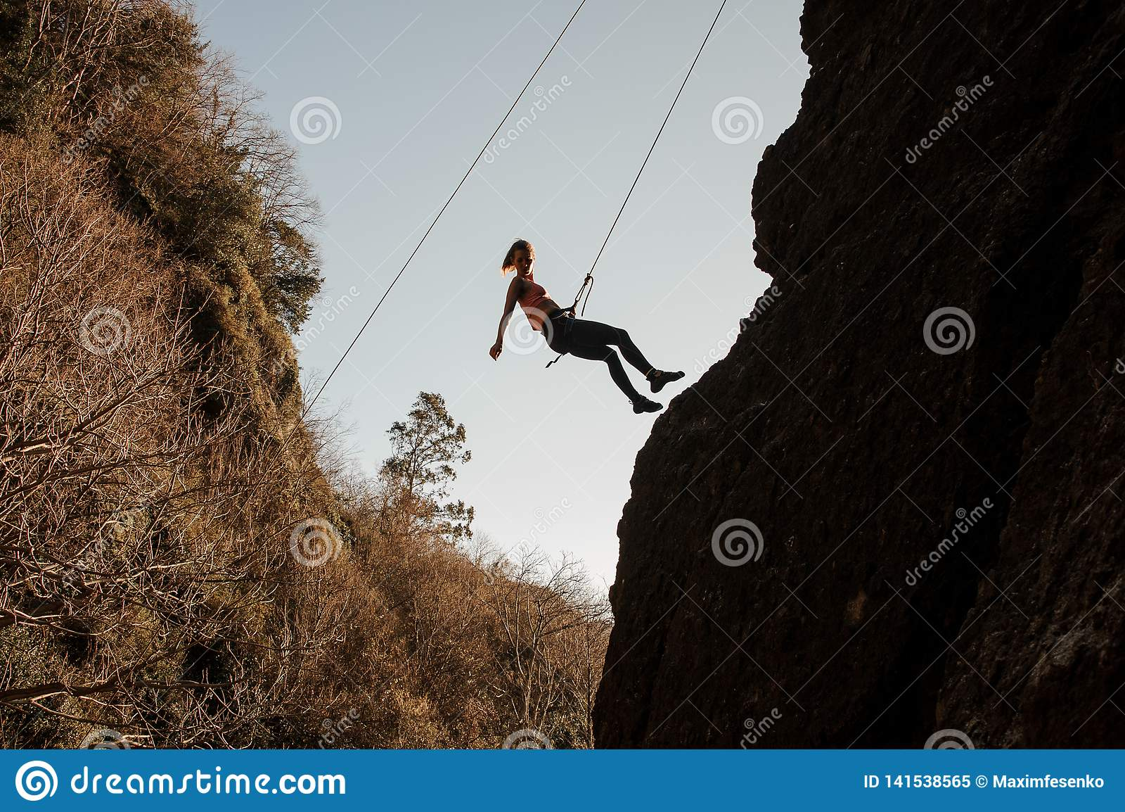Slim fit girl equipped with a rope abseiling on the sloping rock