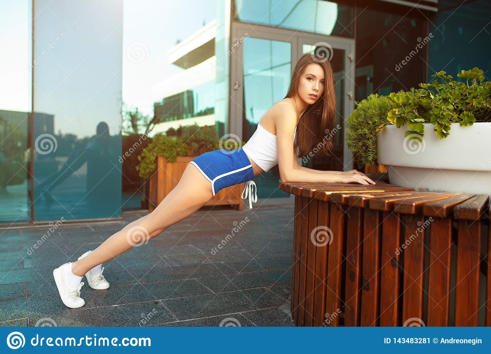 Slim fitness young woman Athlete girl doing plank exercise outside. Concept training workout crossfit gymnastics cross fit
