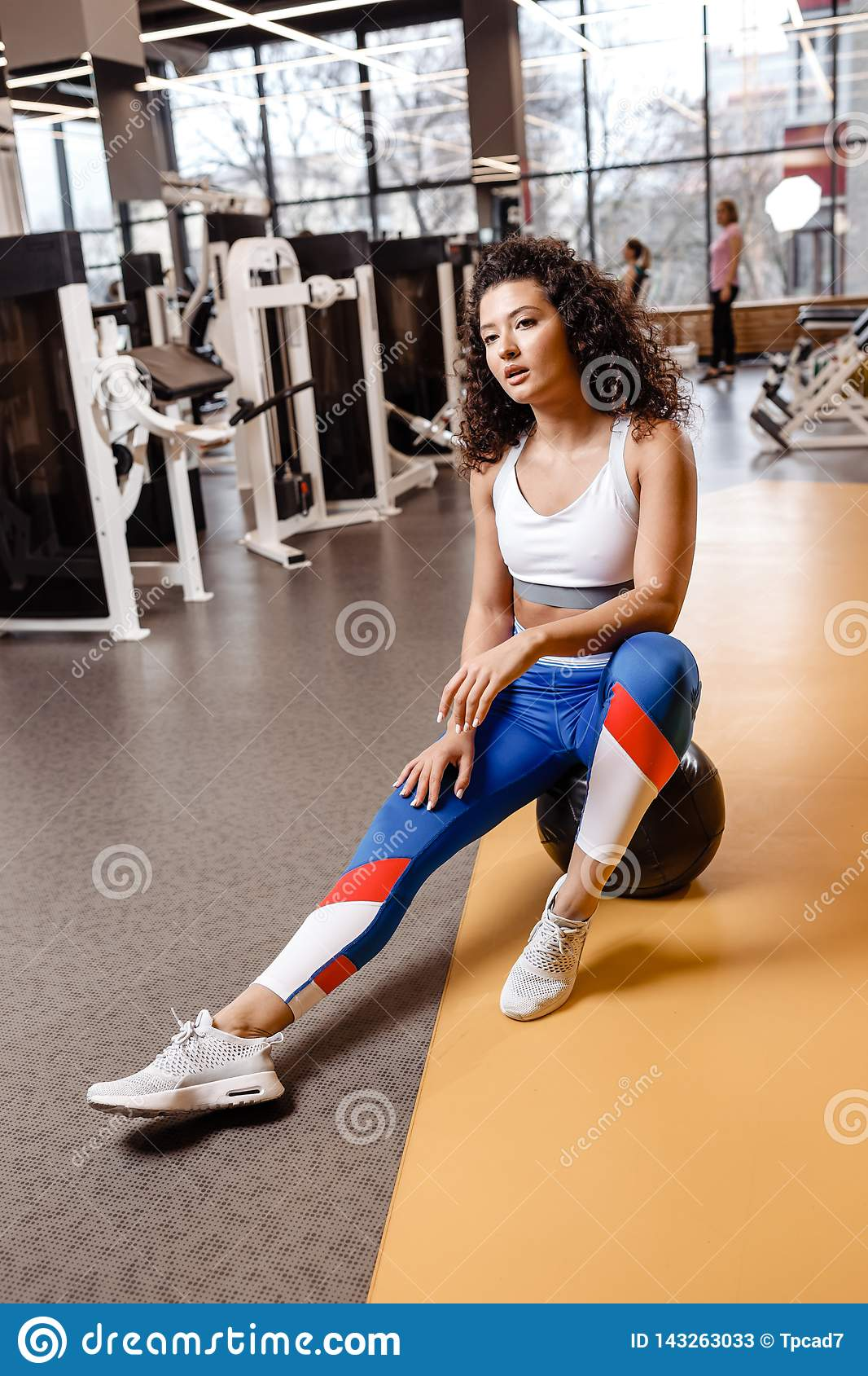 Slim girl with dark curly hair dressed in a sportswear is sitting on the fitness ball in the modern gym with big window