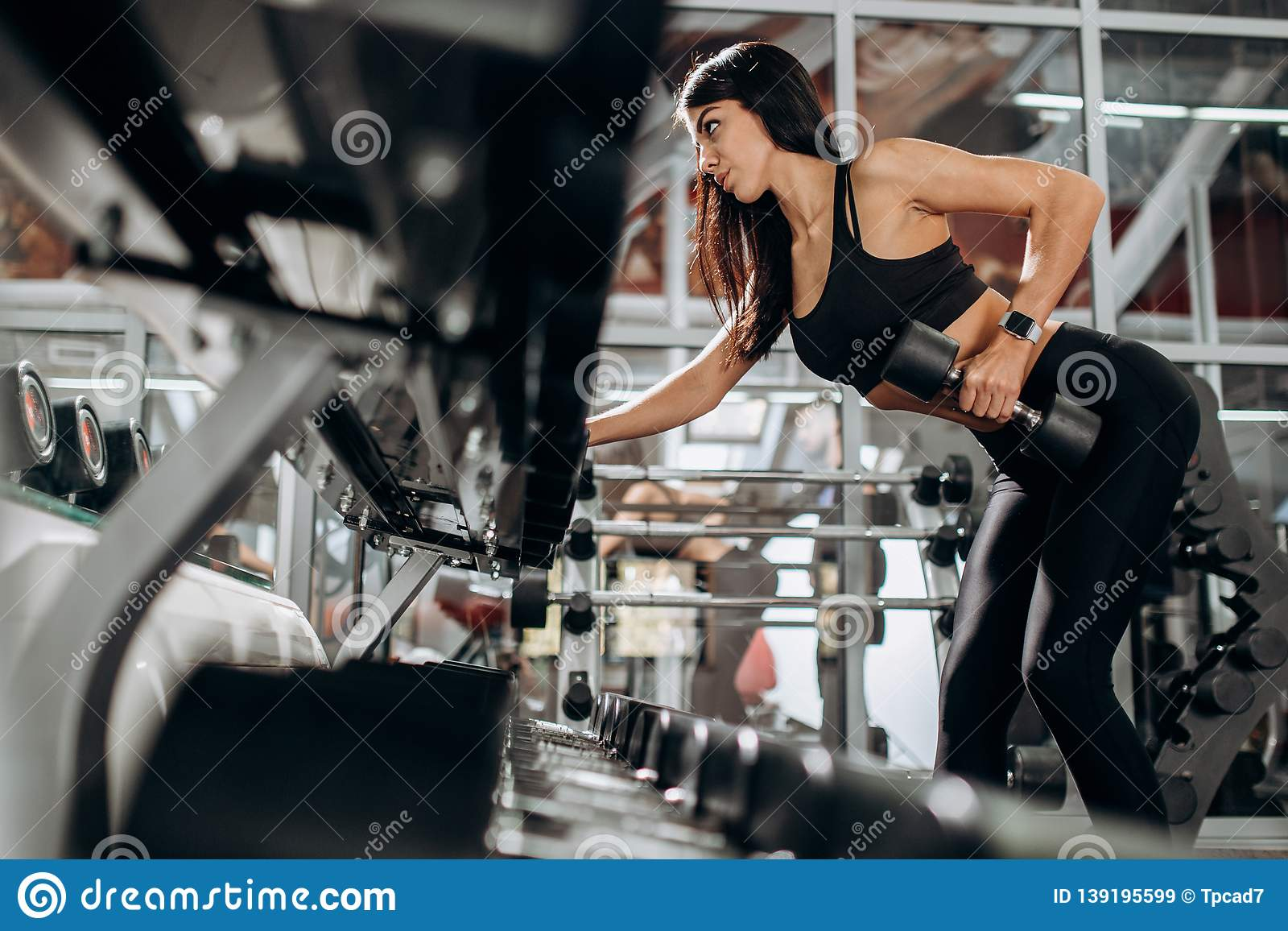 Slim girl dressed in black sport clothes is doing triceps exercise with dumbbell in the gym