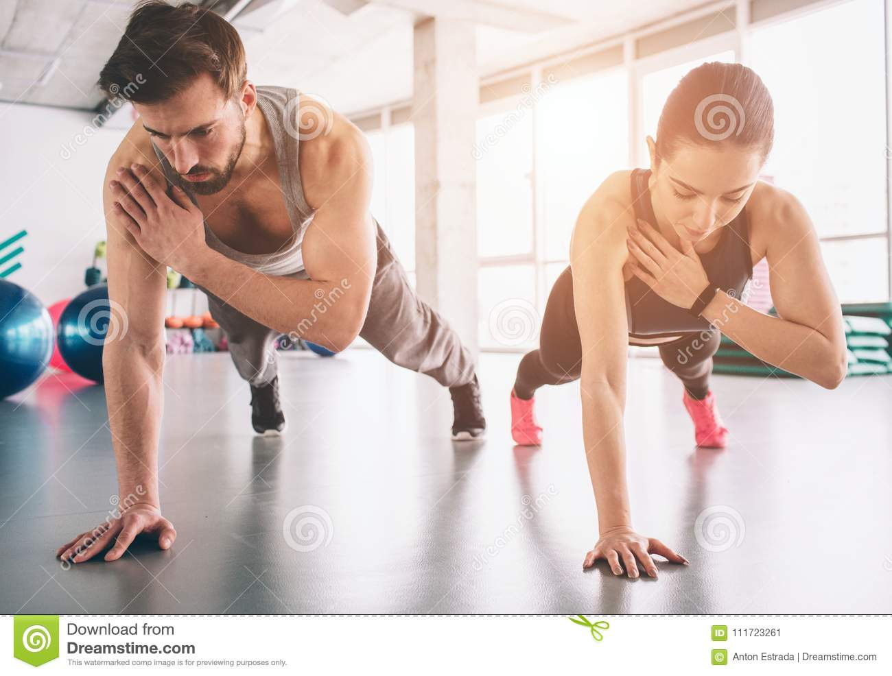 Slim girl and strong man are standing in one hand plank position and balancing on that hand. They look concentrated and