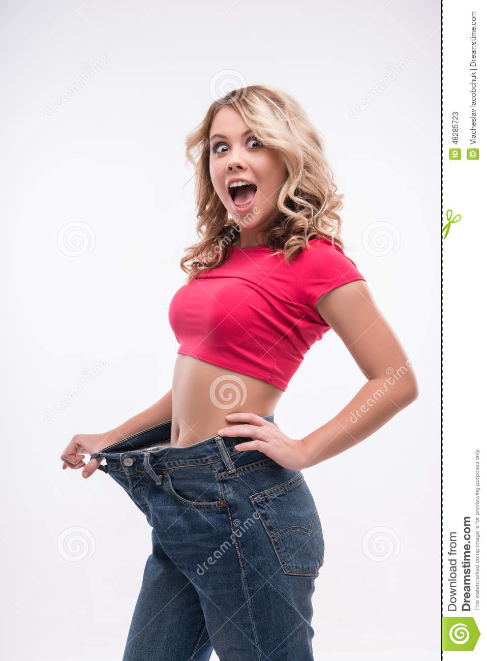 Slim Waist Of Young Woman In Big Jeans Showing Stock Photo