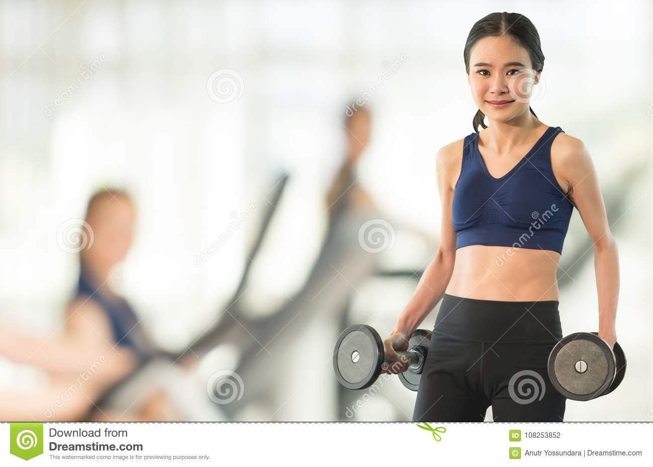 Slim woman holding dumbbell on Blur abstract gym