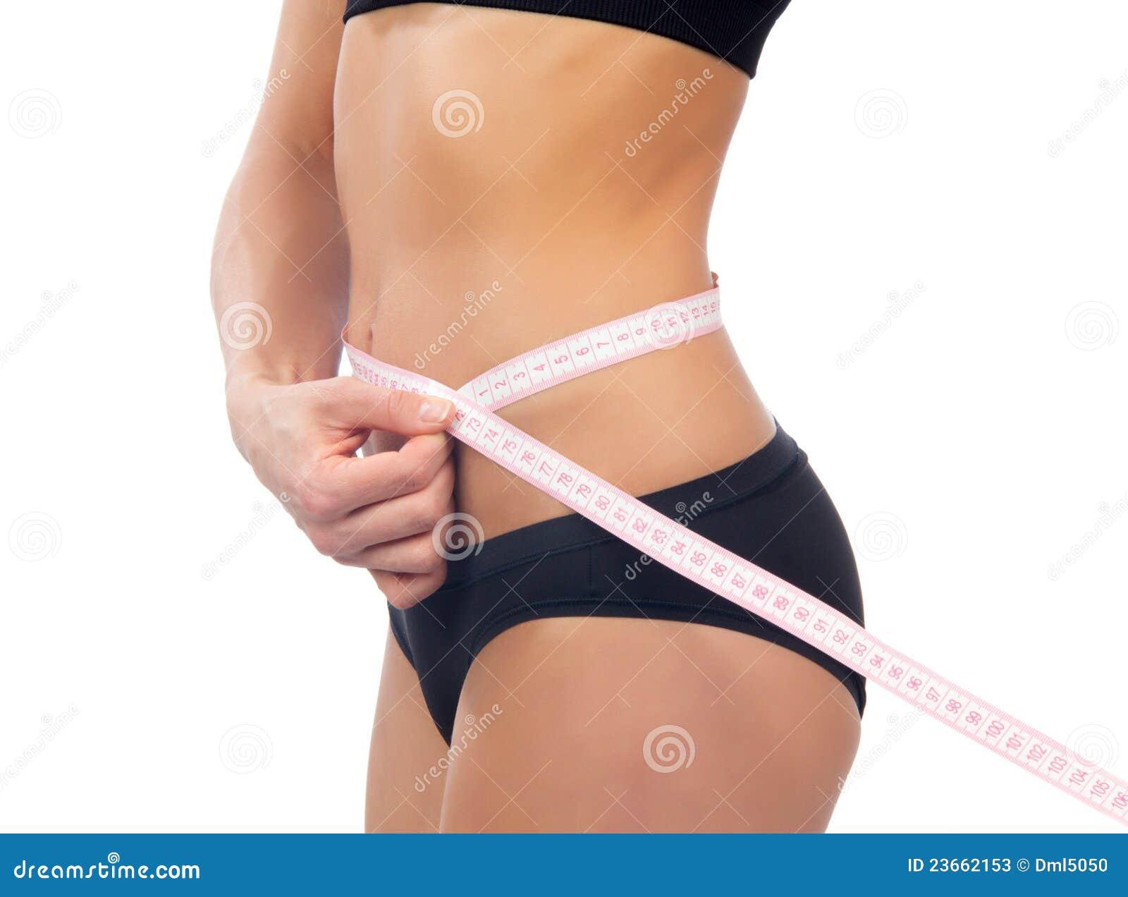 Slim woman measuring her waist metric tape measure