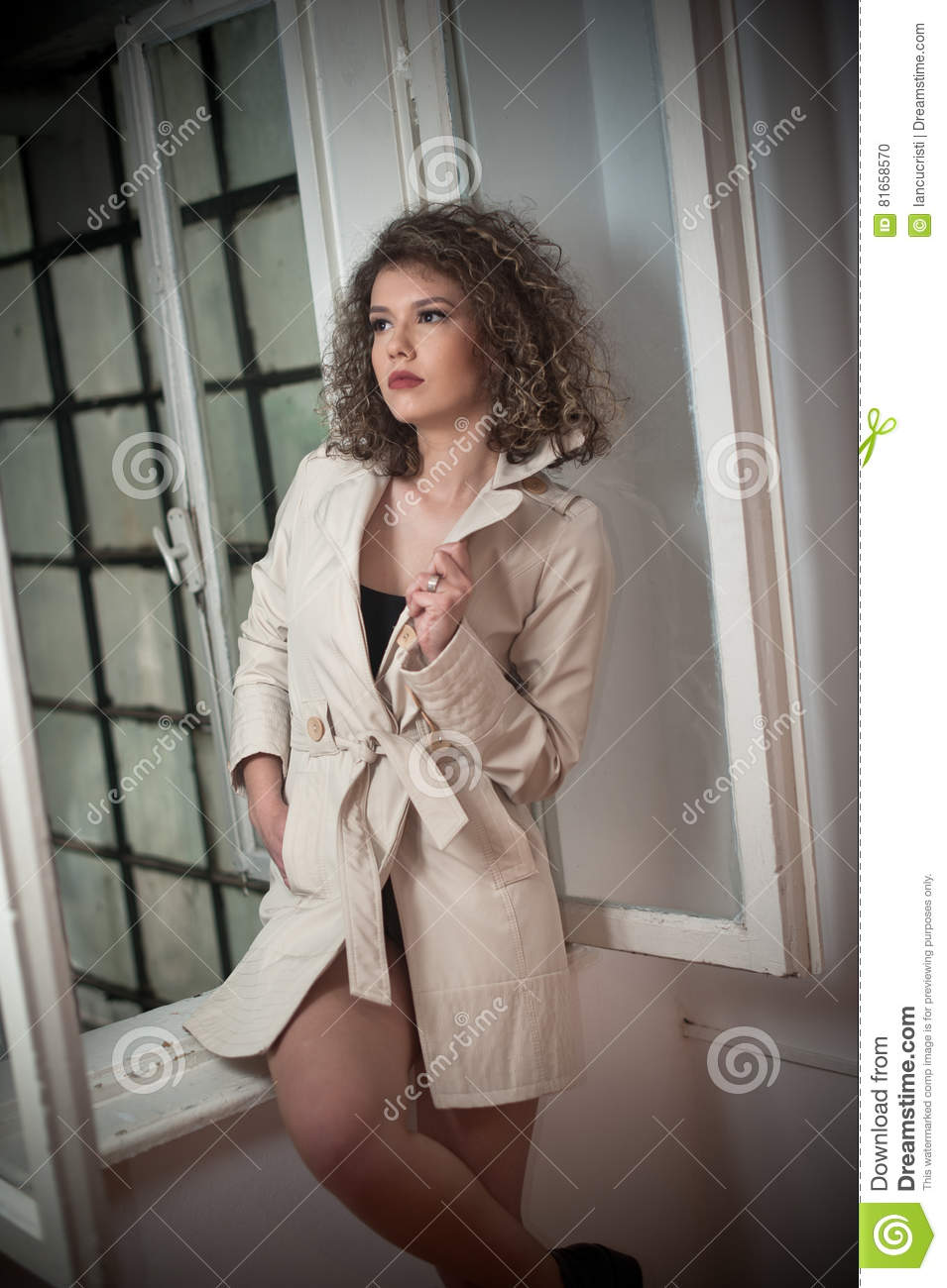 20cf9bb311892 Slim young fashion model wearing white coat in window frame. Lovely  fashionable woman with light brown curly hair. Attractive female