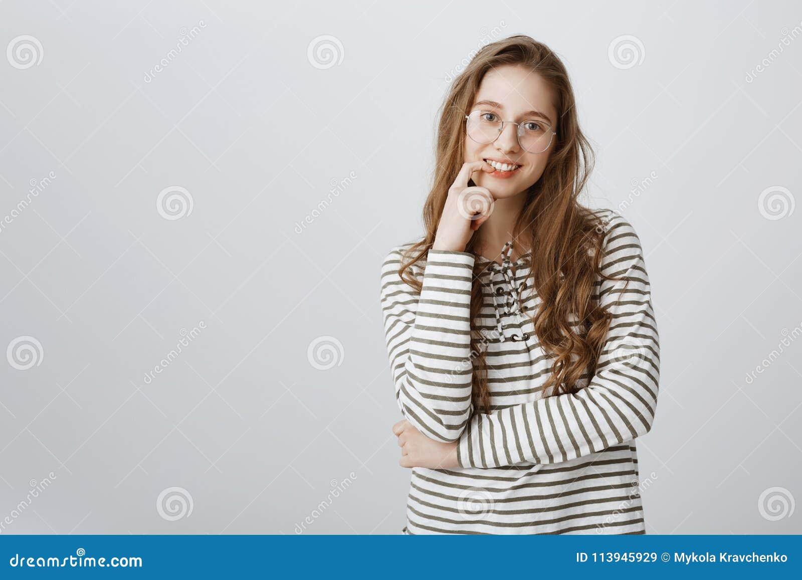 Slimme aantrekkelijke vrouw die met eerlijk haar in gestreept sweatshirt en transparante glazen, vinger houden ruim glimlachen di