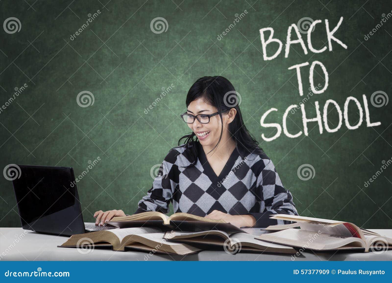 Slimme student die laptop en boeken in klasse gebruiken