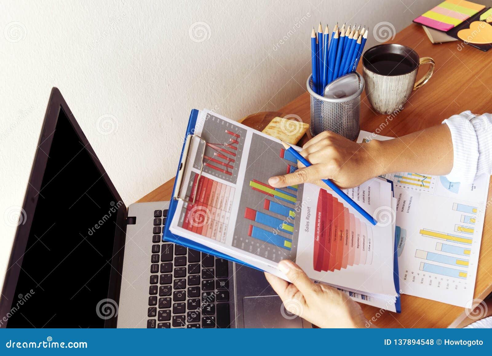 Slimme werkende vrouw bij haar bureau met documenten en laptop Onderneemster die aan administratie werken