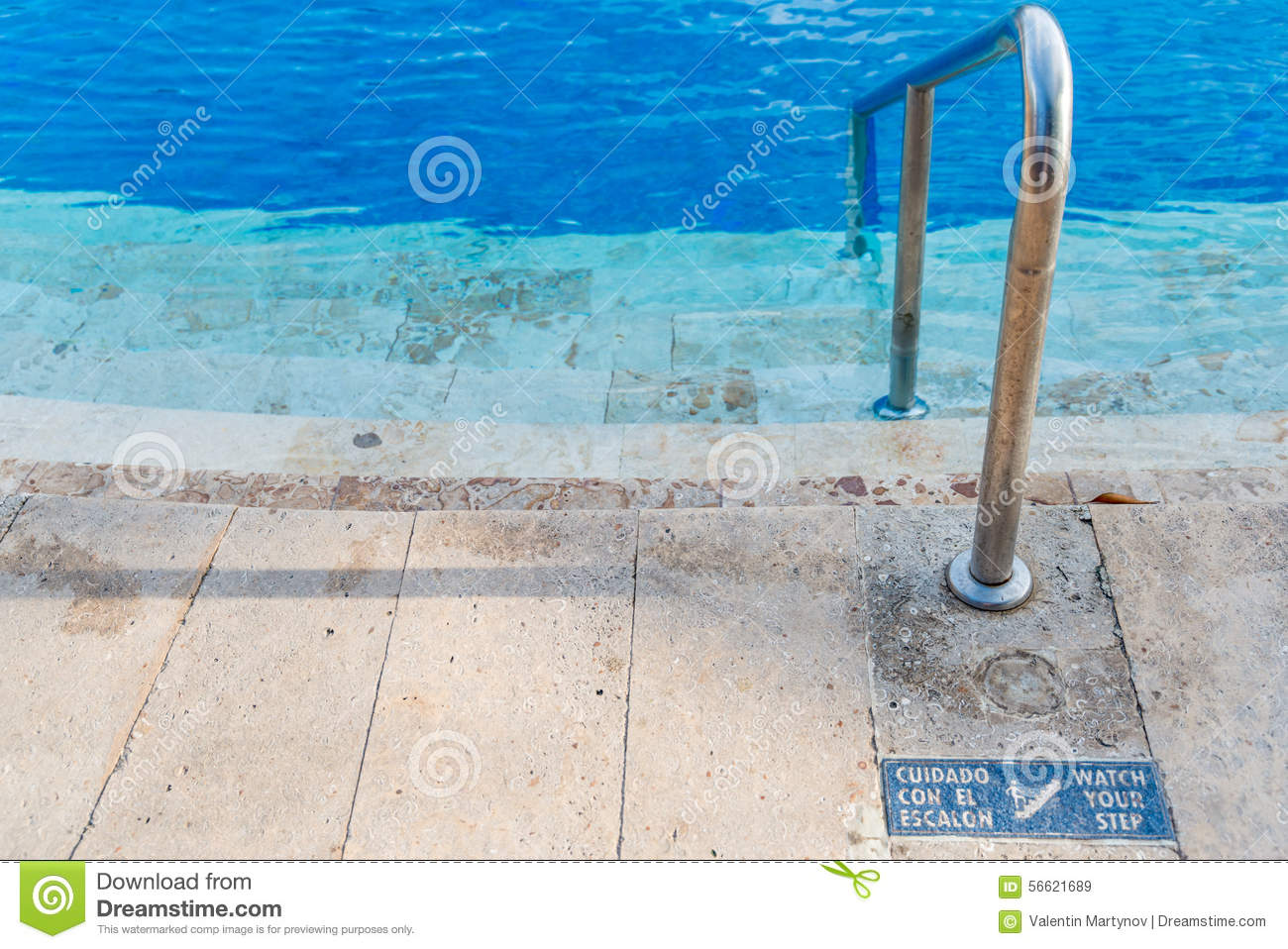Slippery Steps Down To Swimming Pool With Blue Water And Watch Your Step Sign In Both English