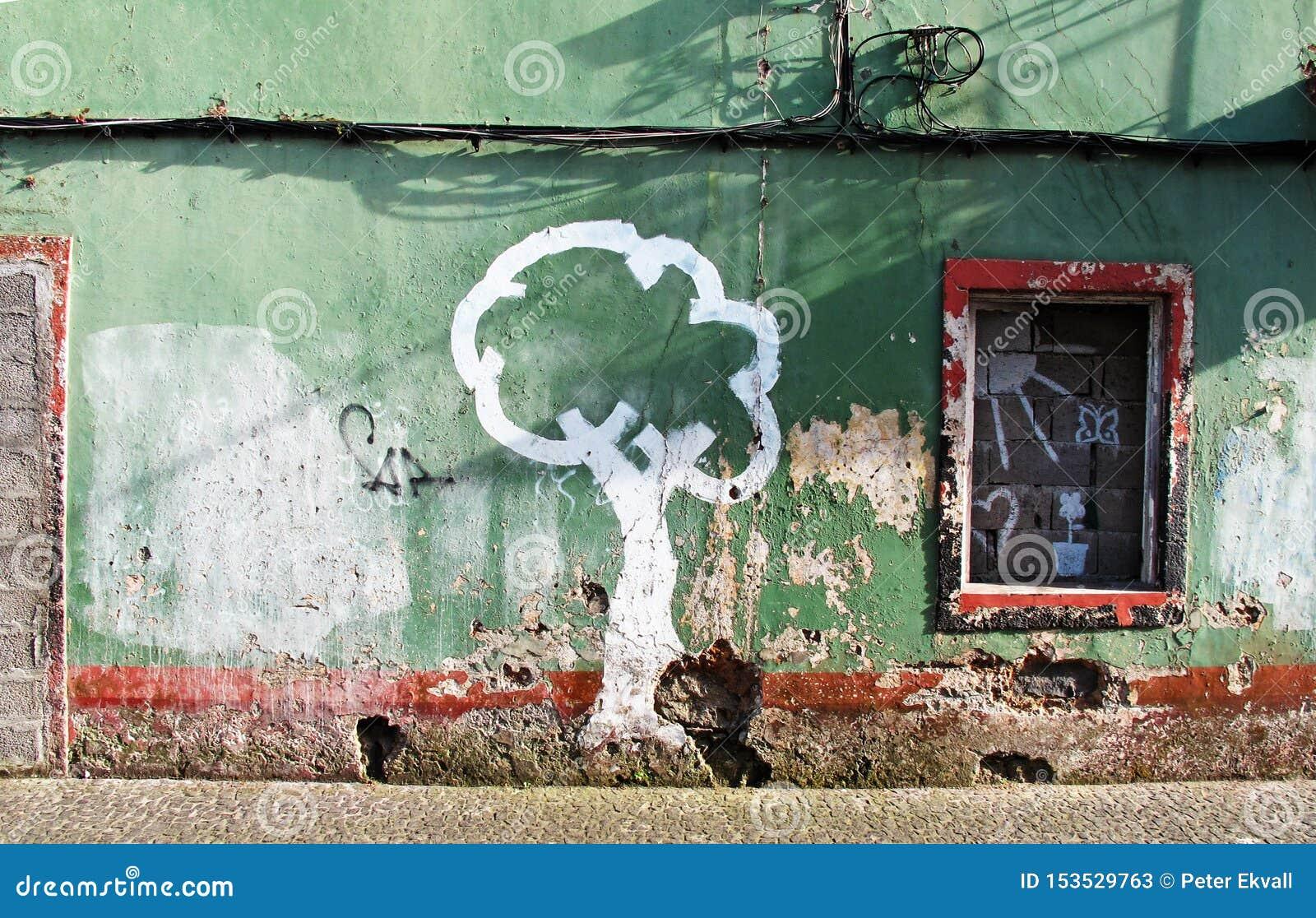 Slitna hus i gräsplan och ett målat träd i vit