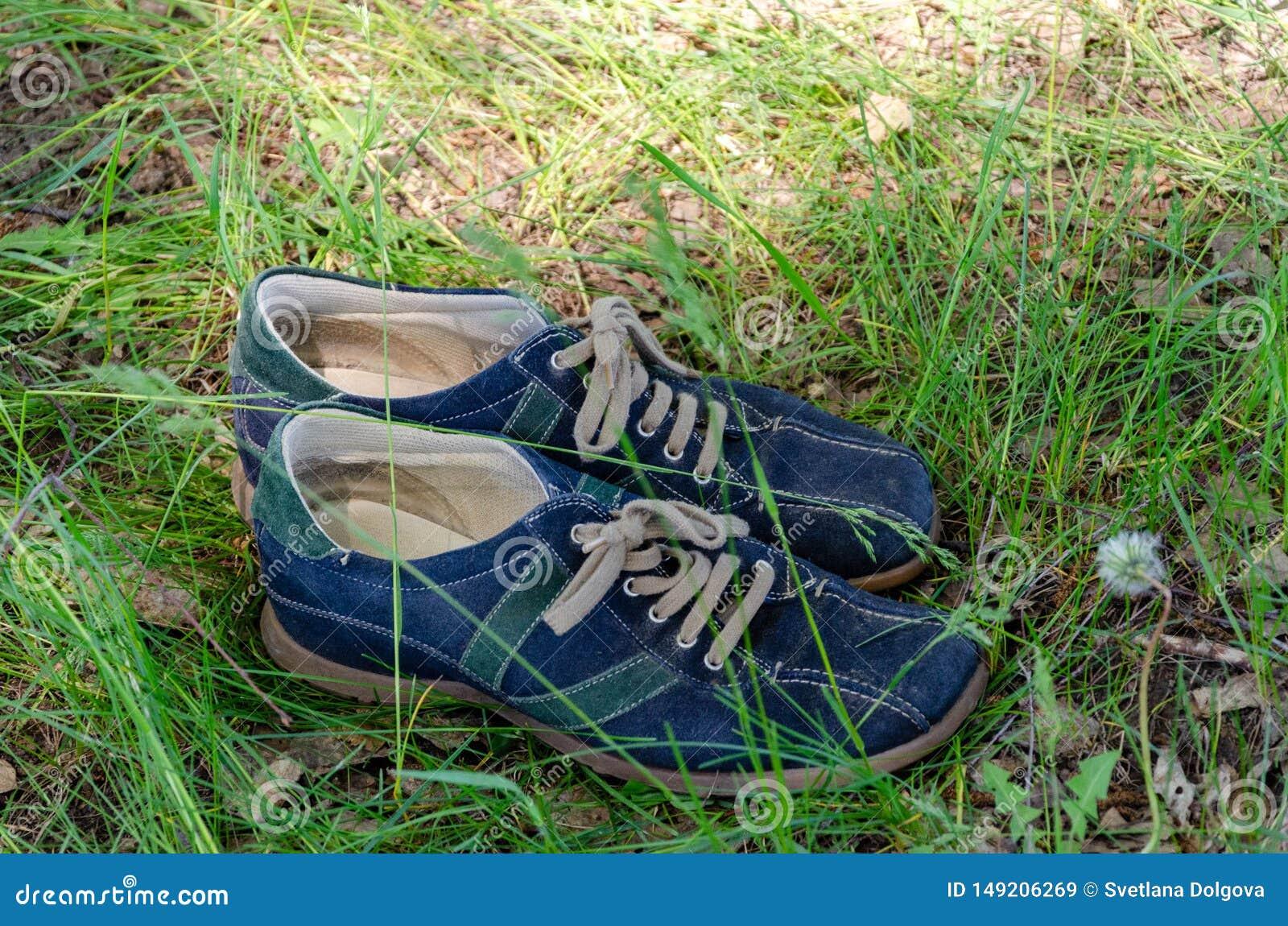 Slitna skor p? gr?s i en sommarskog