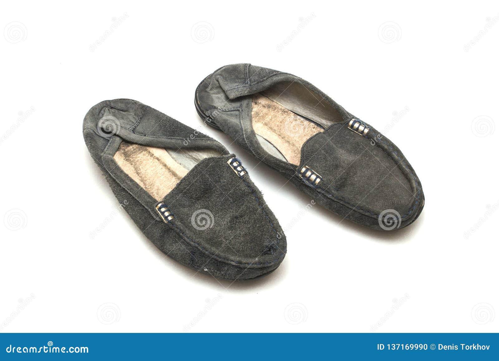 Slitna ut kvinnliga skor på vit isolerad bakgrund