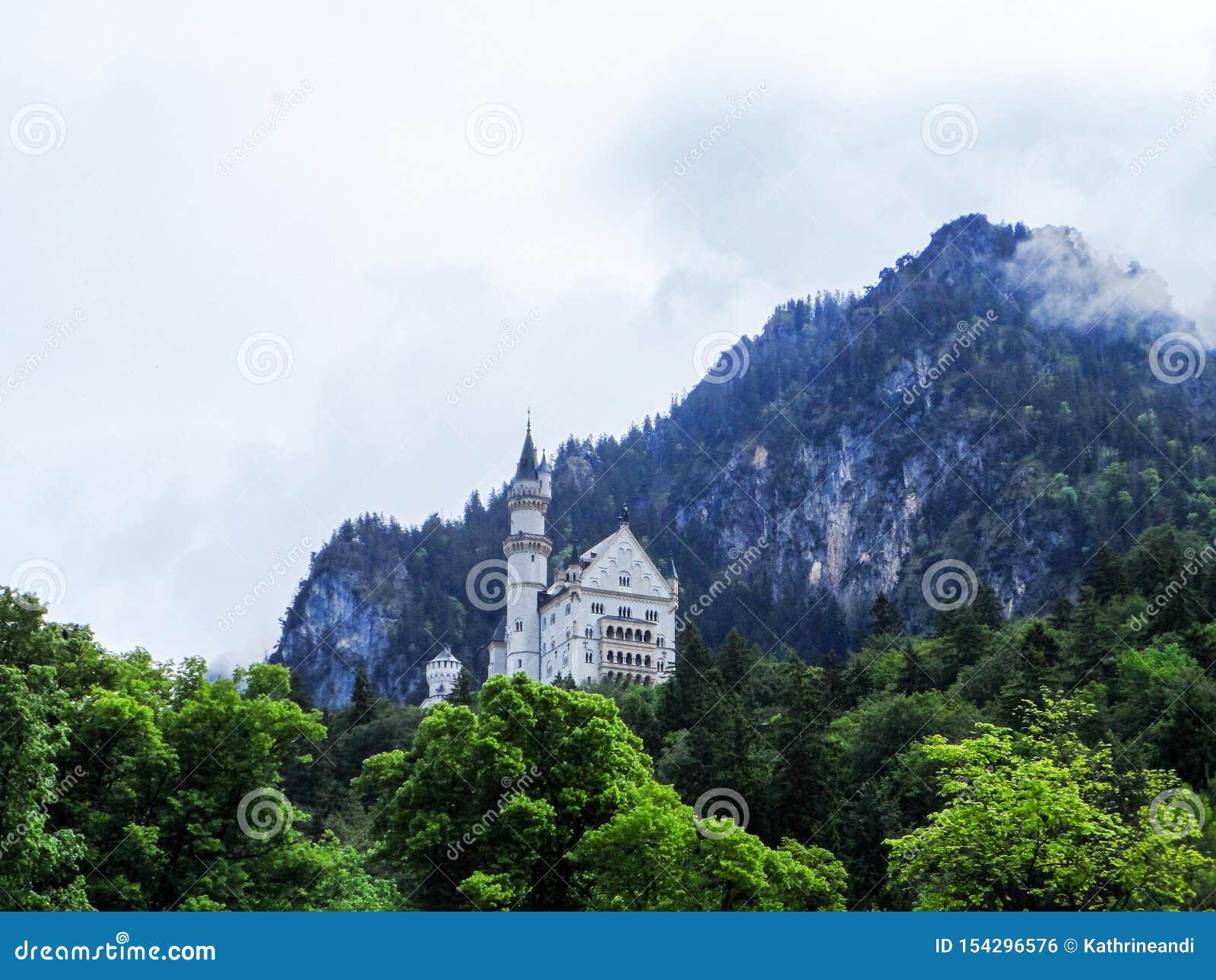 Slott av Neuschwanstein, Tyskland Sikt från sjön med träd, moln och berg på bakgrund
