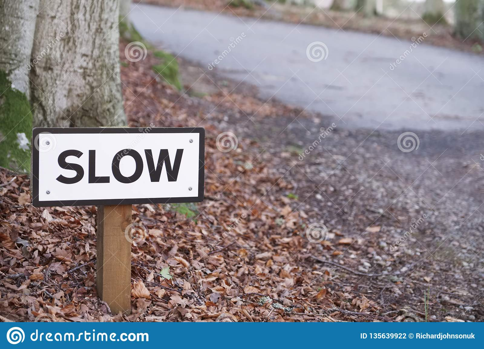 Slow down road safety sign on rural countryside highway uk