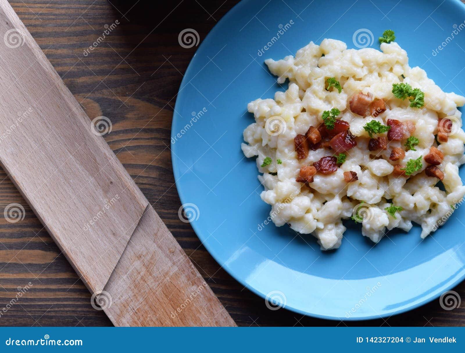 Slowaakse traditionele aardappelgnocchi met schapenkaas en bacon, houten lijst