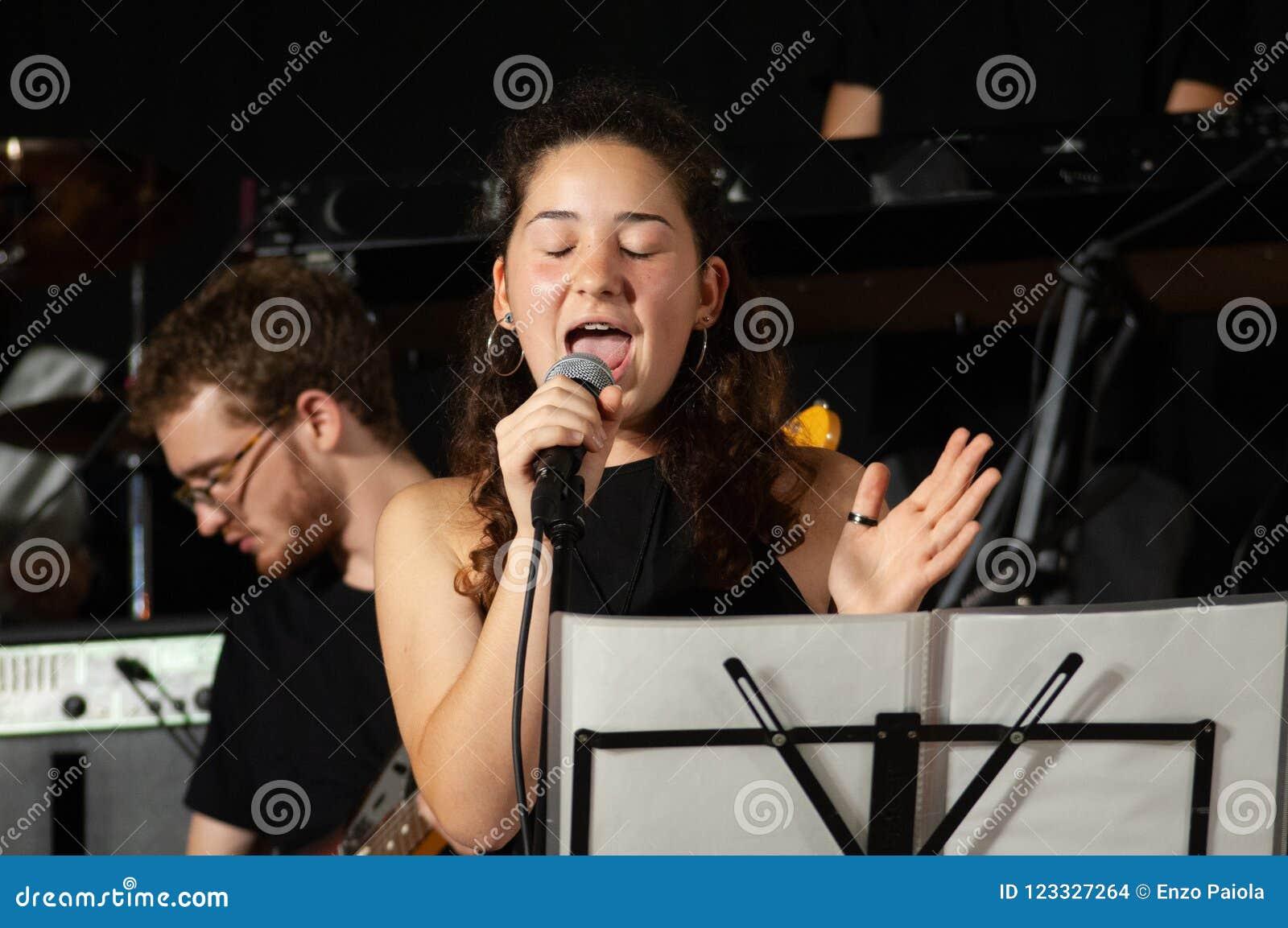 Sluit gezichts omhoog mooi jong brunette, vocalistzanger met microfoon, terwijl zingen levend, met jonge gitarist op achtergrond