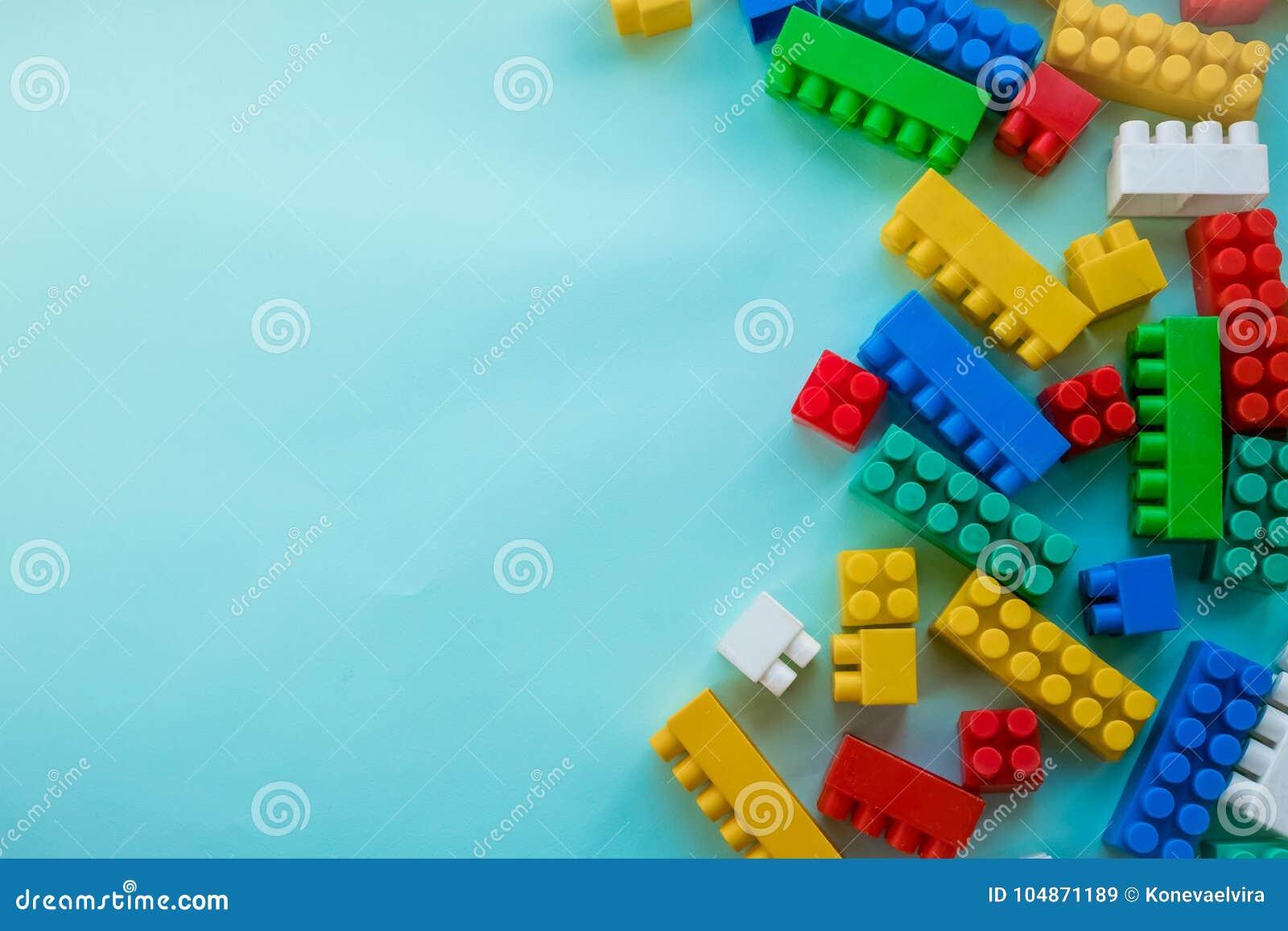 Sluit Kinderen omhoog plastic aannemer op een blauwe achtergrondstreepachtergrond Het ontwikkelen van speelgoed