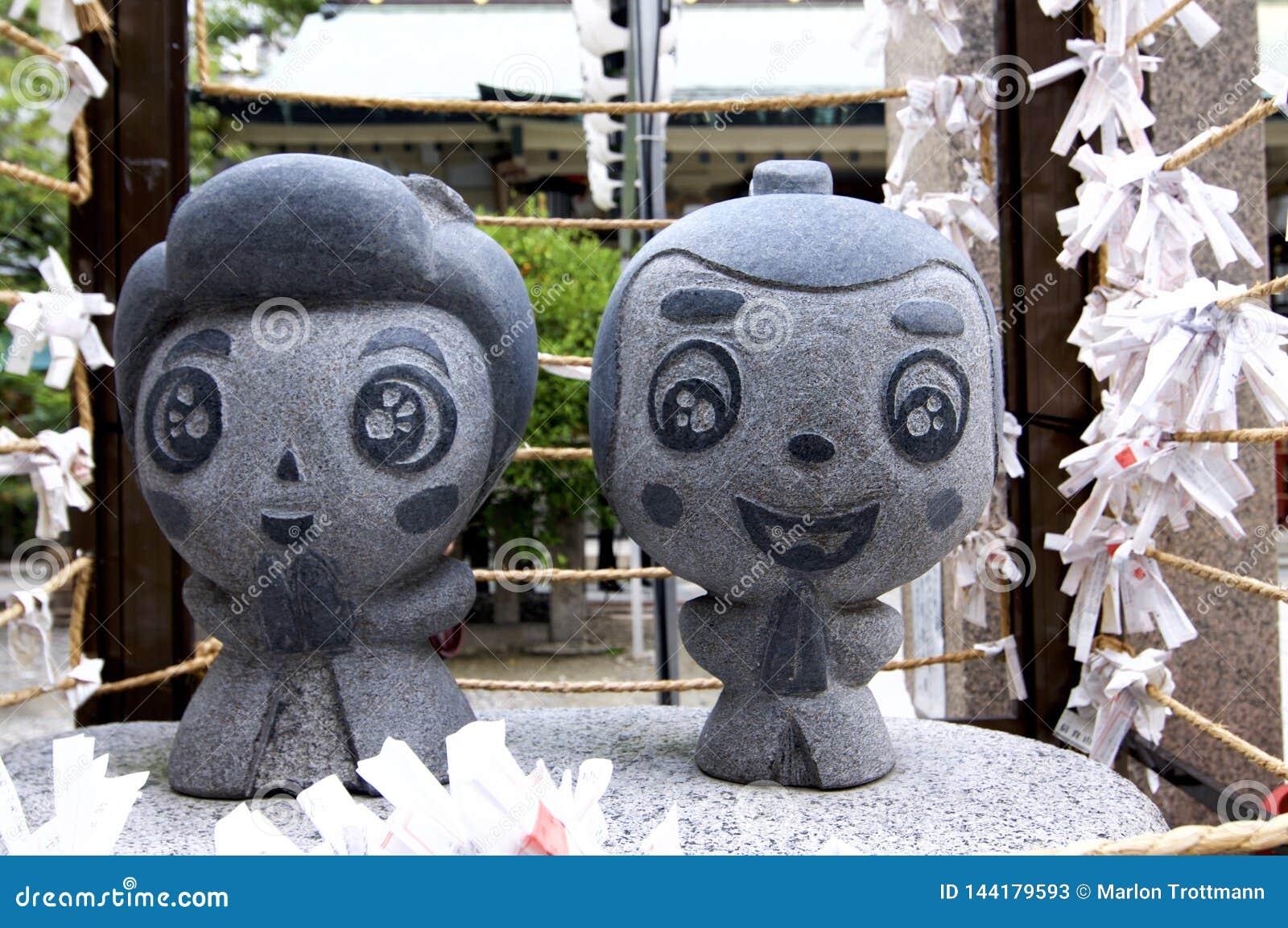 Sluit omhoog beeld van het kleine de steenstandbeeld van Ohatsu en Tokube-bij het Tsuyunoten-Heiligdom in Osaka