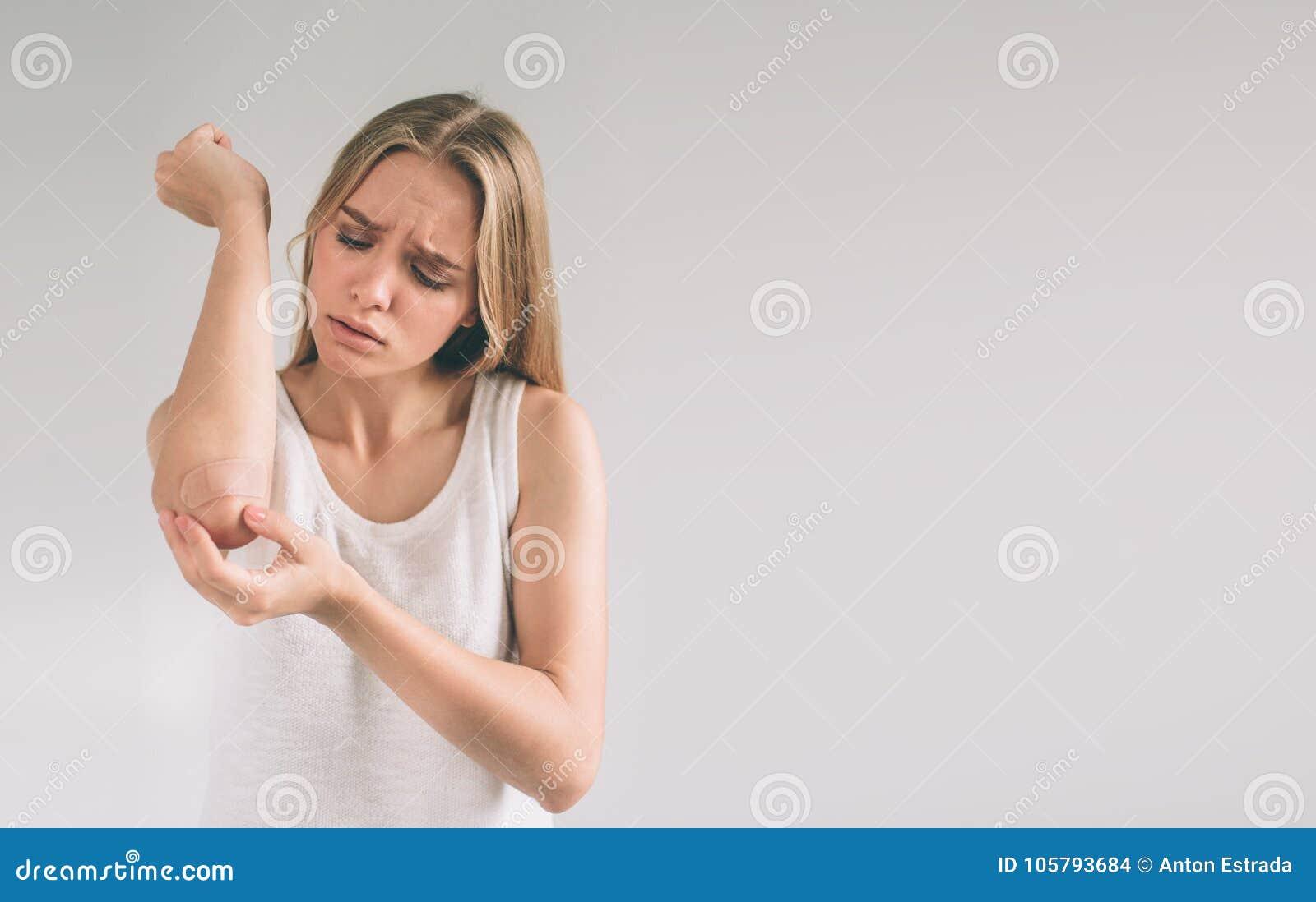 Sluit omhoog bruin verband of pleister op een verwonde die elleboog op witte achtergrond wordt geïsoleerd Vrouw die zelfklevend v