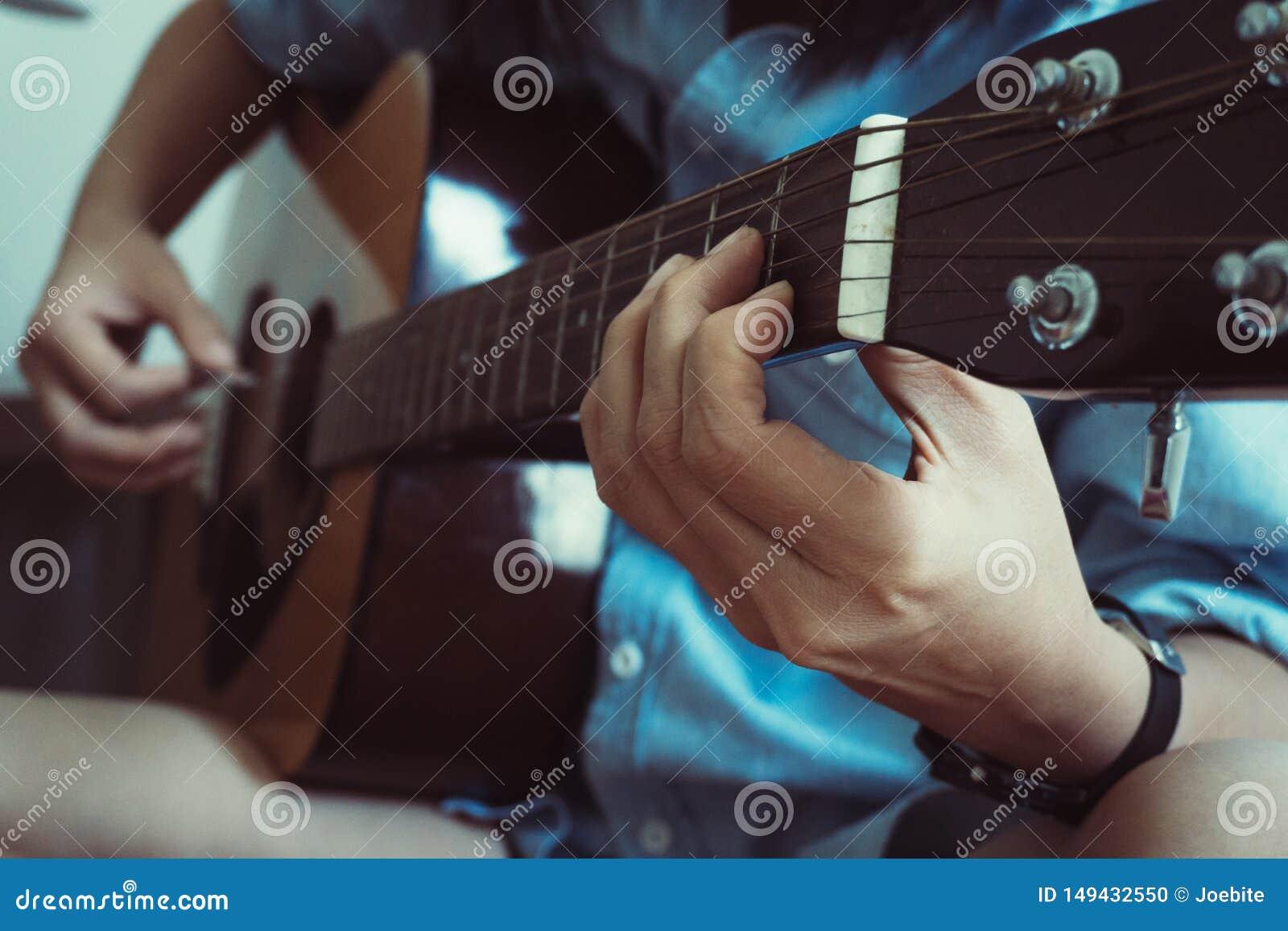 Sluit omhoog de hand van de mooie jonge Aziatische vrouw spelend akoestische gitaar terwijl thuis het zitten op bank Het concept
