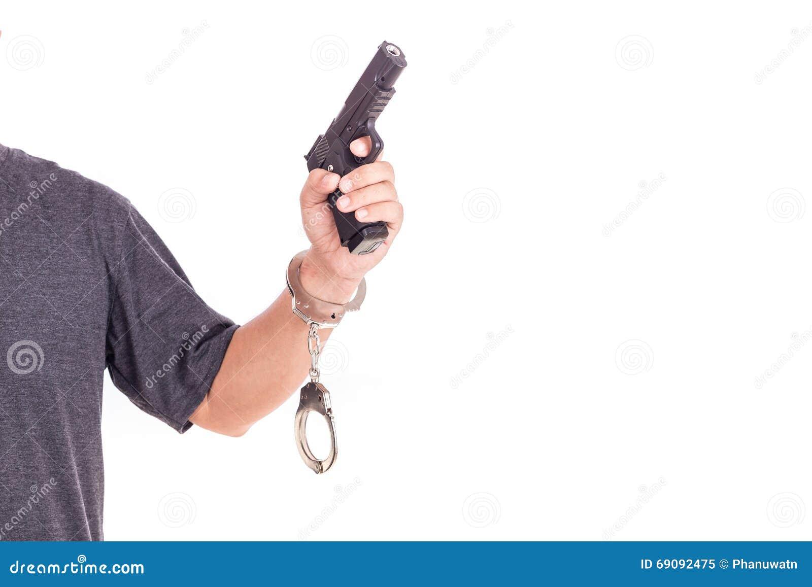 Sluit omhoog de mens met handcuffs en kanon op handen op wit worden geïsoleerd dat